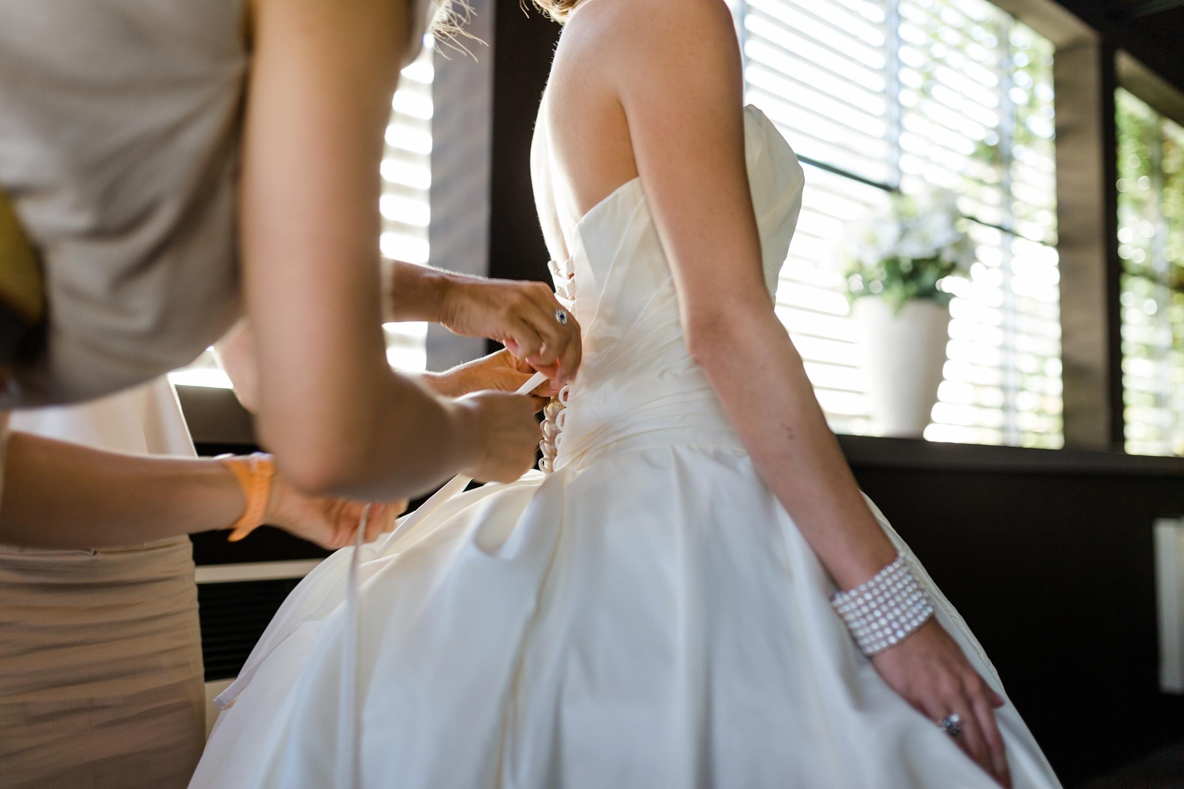 Hochzeitsreportage-Zuerich-Braut-Getting-Ready-Brautkleid-schnueren-Giardino-Verde-Uitikon