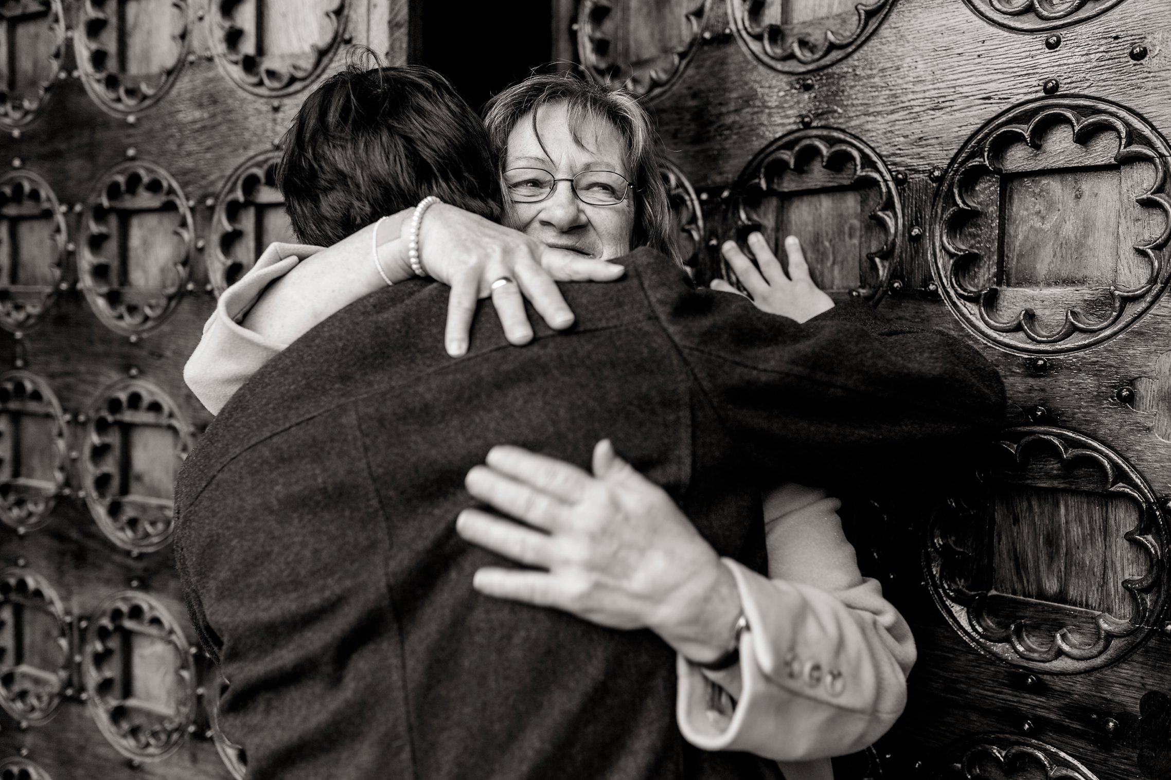 Die Mutter des Bräutigams umarmt ihren Sohn noch einmal innig vor der kirchlichen Trauung.