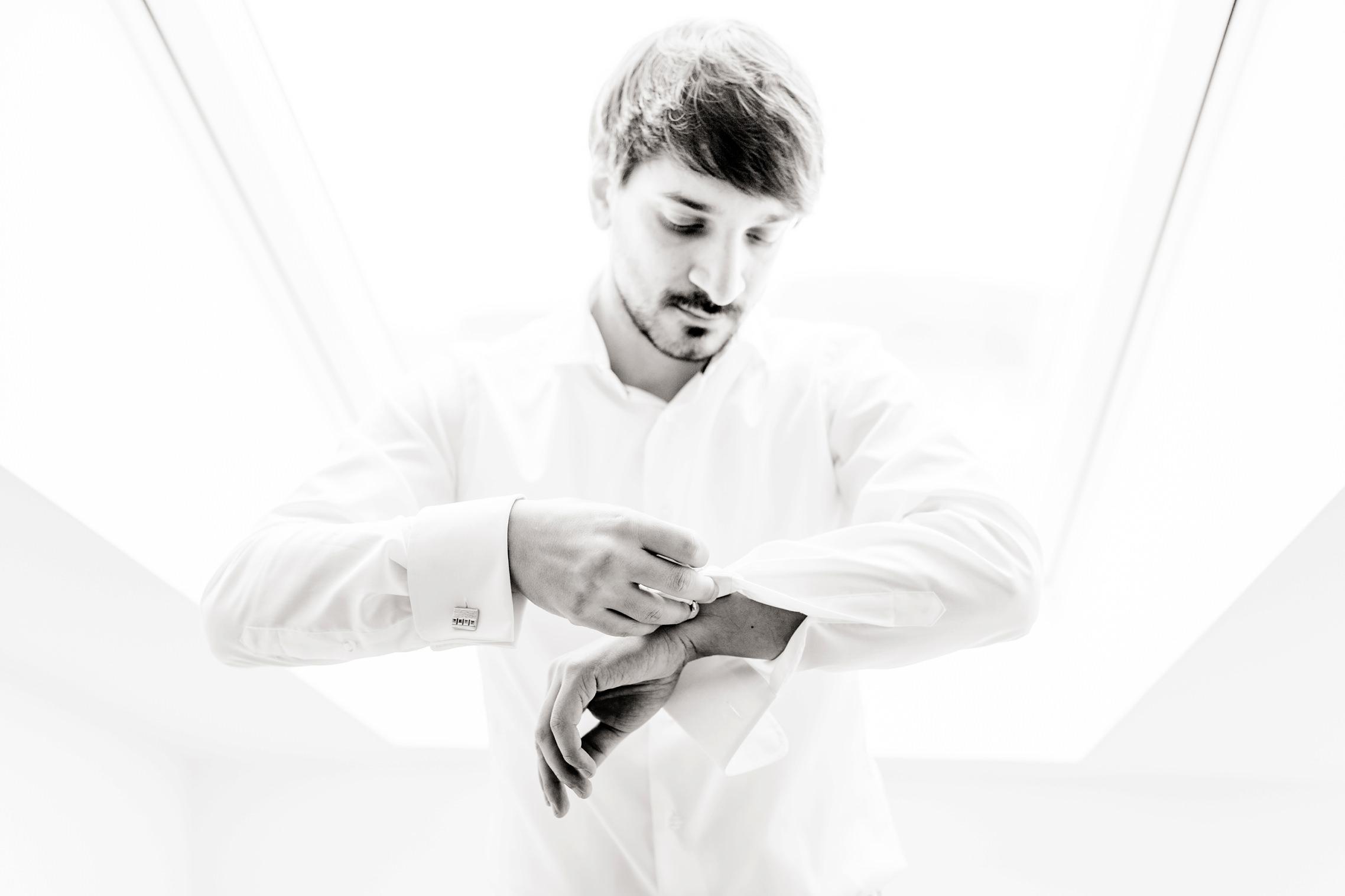 Schwarzweiss-Portrait des Bräutigams, der sich die Manschettenknöpfe anlegt