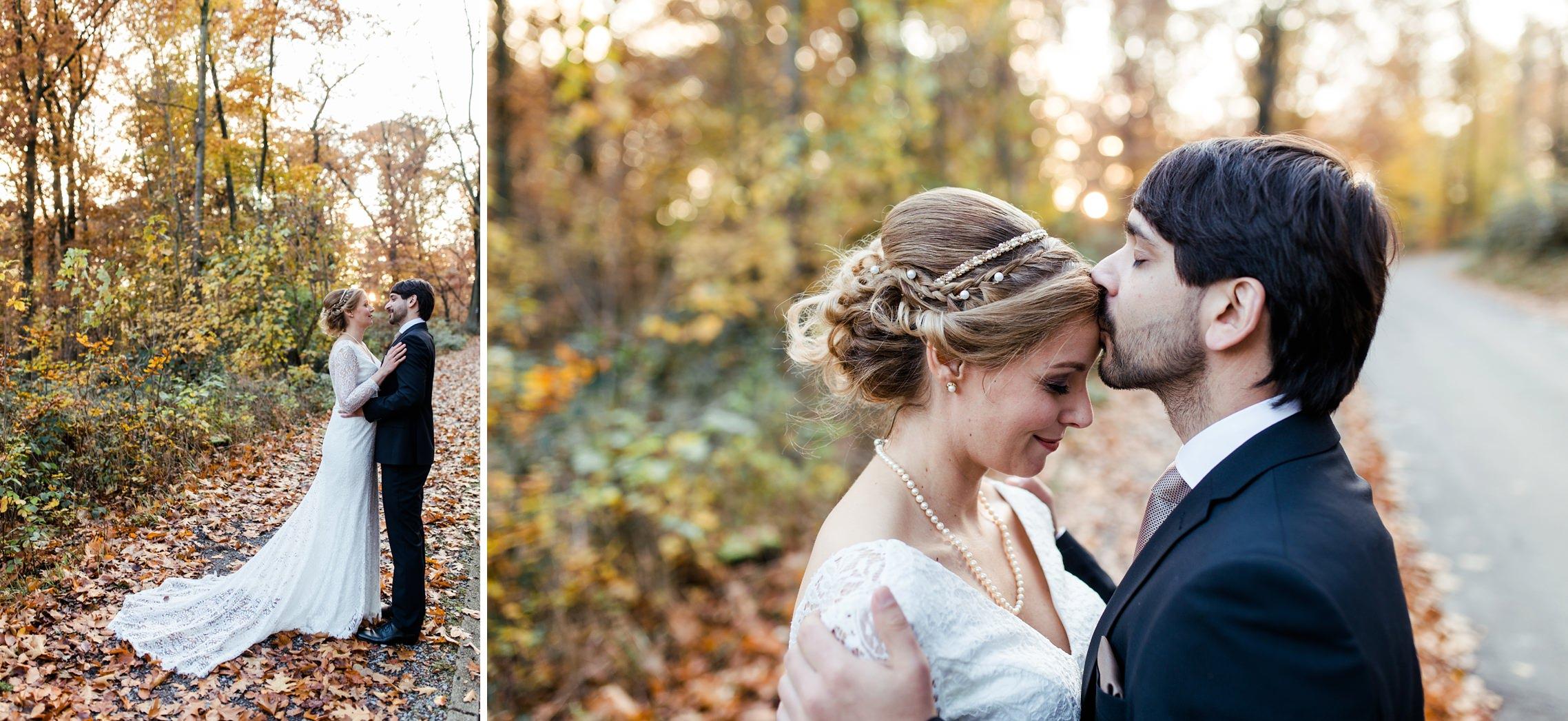 Der Bräutigam küsst seine Braut auf die Stirn beim Hochzeits-Shooting im herbstlichen Laubwald