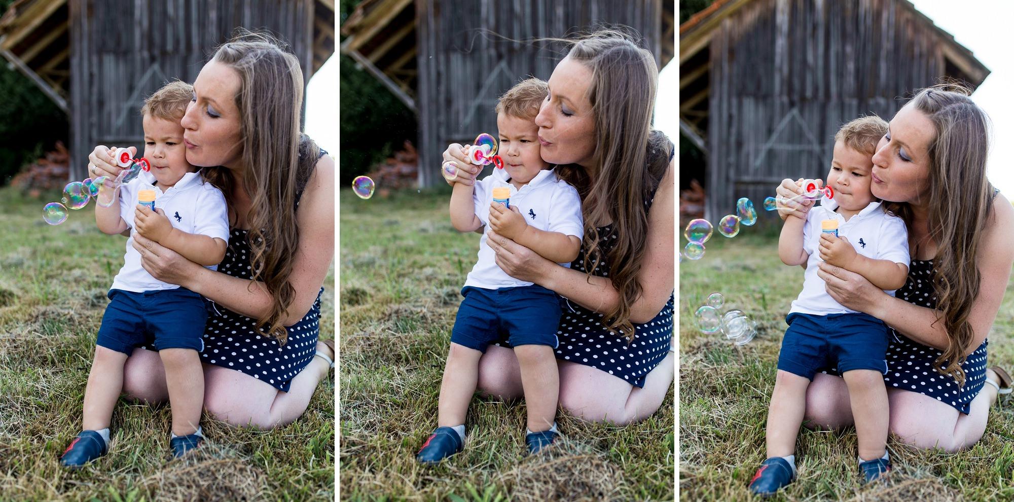 Kleinkind pustet Seifenblasen mit Mutter