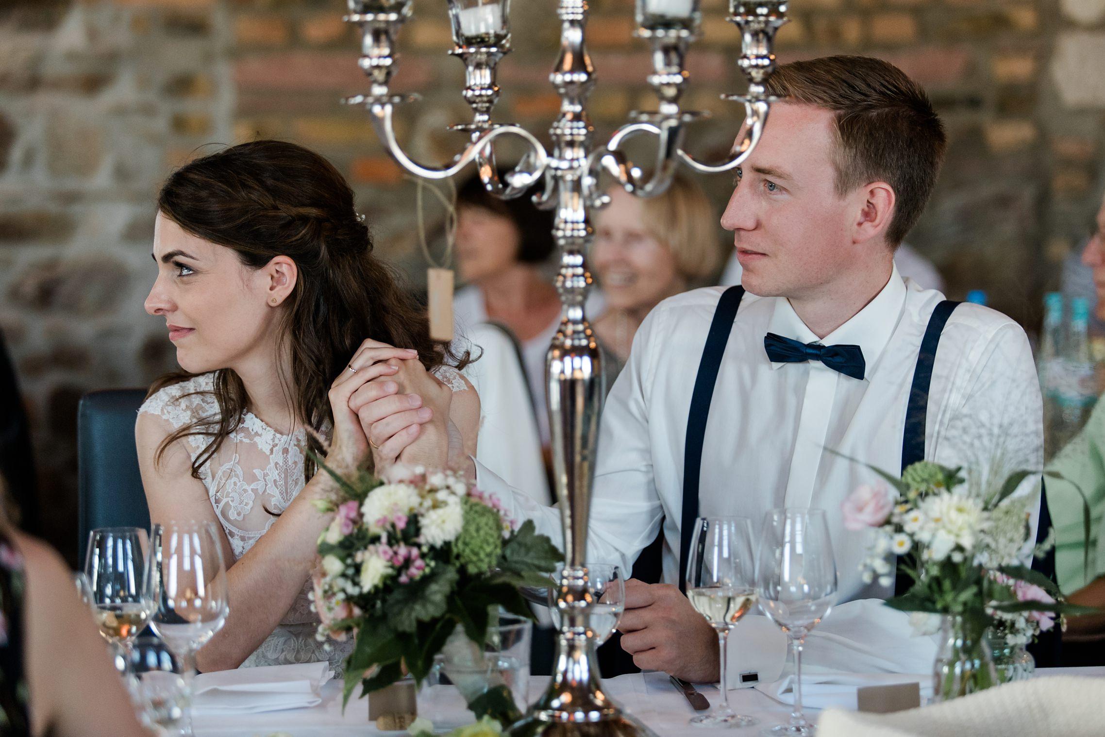 Das Brautpaar hört aufmerksam der Rede des Brautvaters zu und hält sich an den Händen