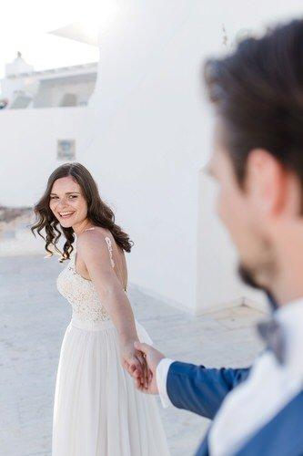 Braut zieht Bräutigam an der Hand