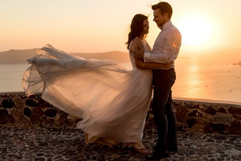 Brautpaar mit wehendem Kleid im Sonnenuntergang