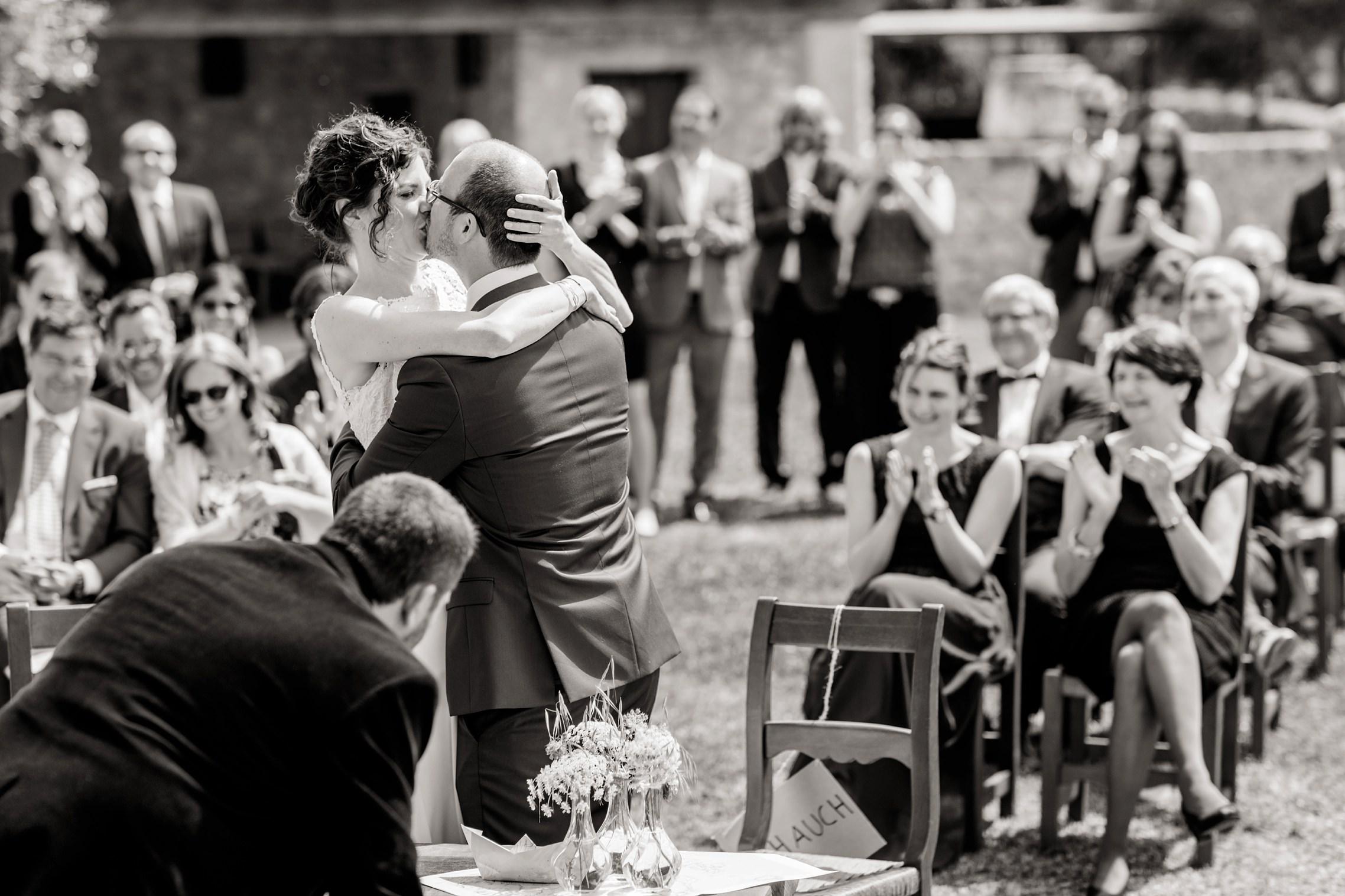 Schwarzweiss-Bild des Brautpaares, welches sich nach der Trauung küsst.
