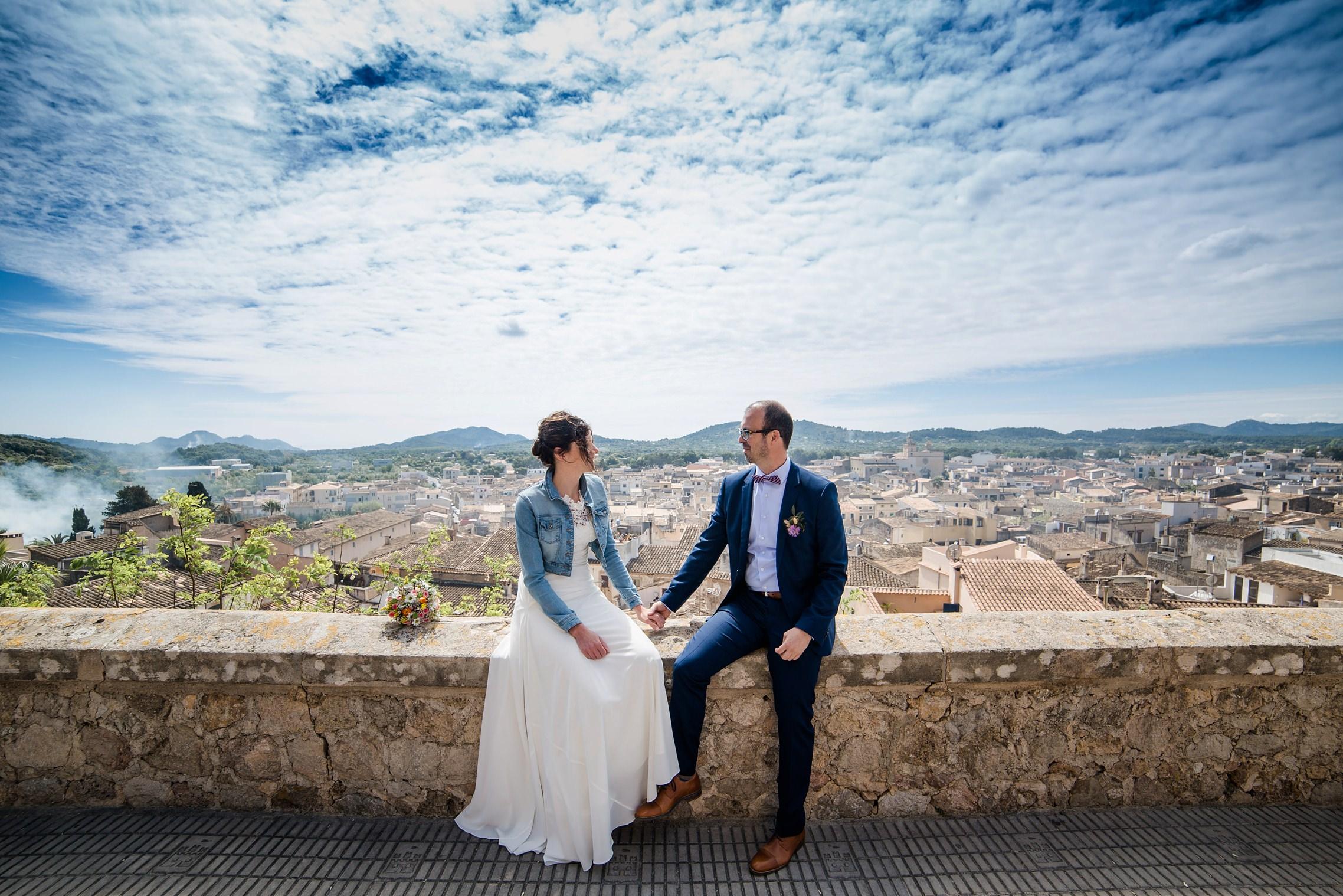 Ein verliebtes Brautpaar schaut sich in die Augen über den Dächern von Artá auf Mallorca