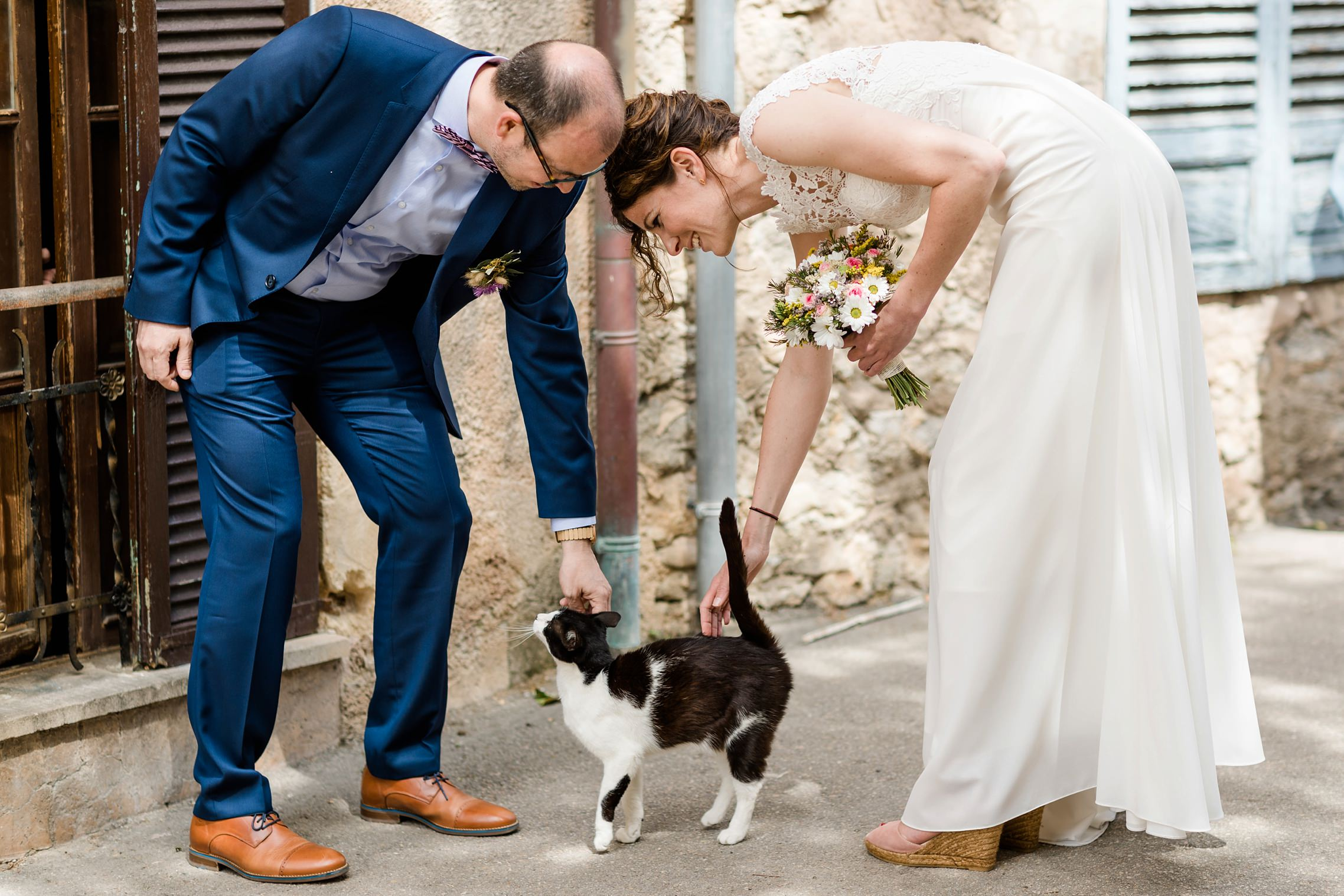 Braut und Bräutigam streicheln eine Katze in den Gassen von Artá, Mallorca
