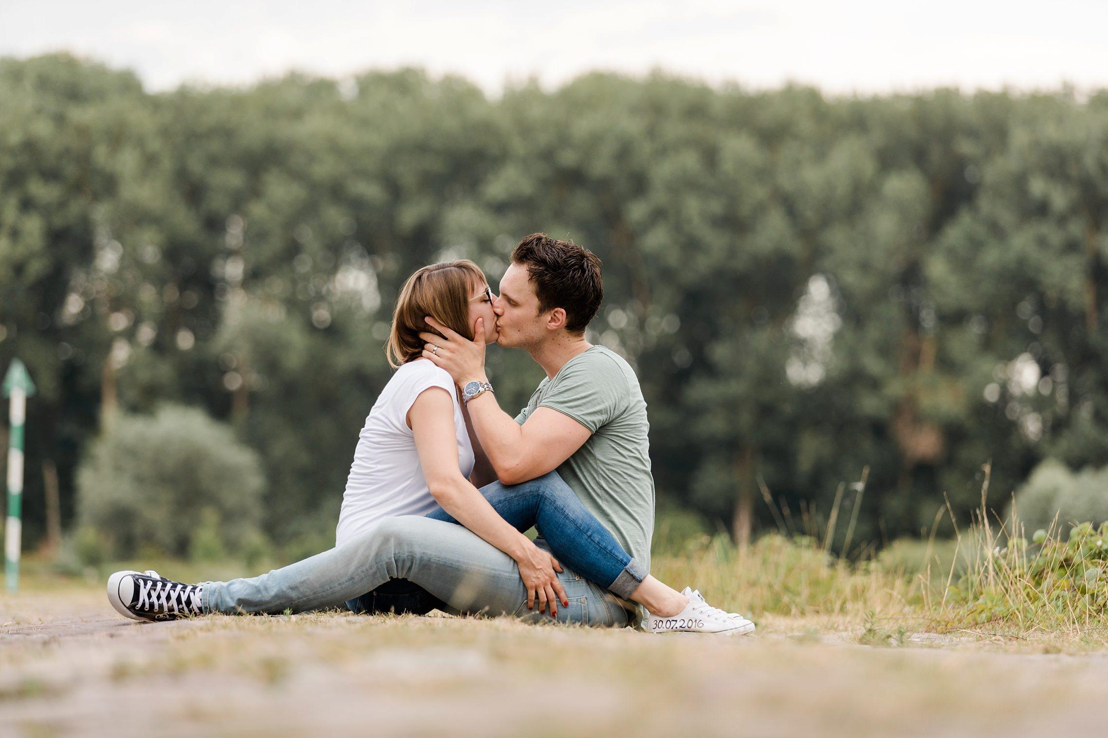Romantische Pärchenfotos: Verliebtes Paar sitzt auf dem Boden und küsst sich innig