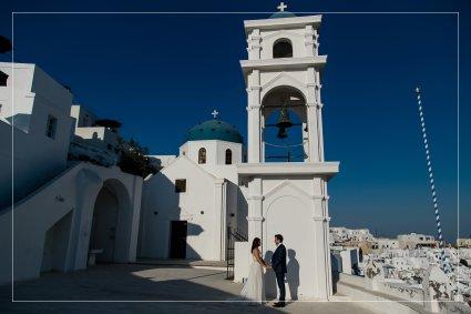 Hochzeitspaar vor weißer Kirche und blauem Himmel auf Santorini.