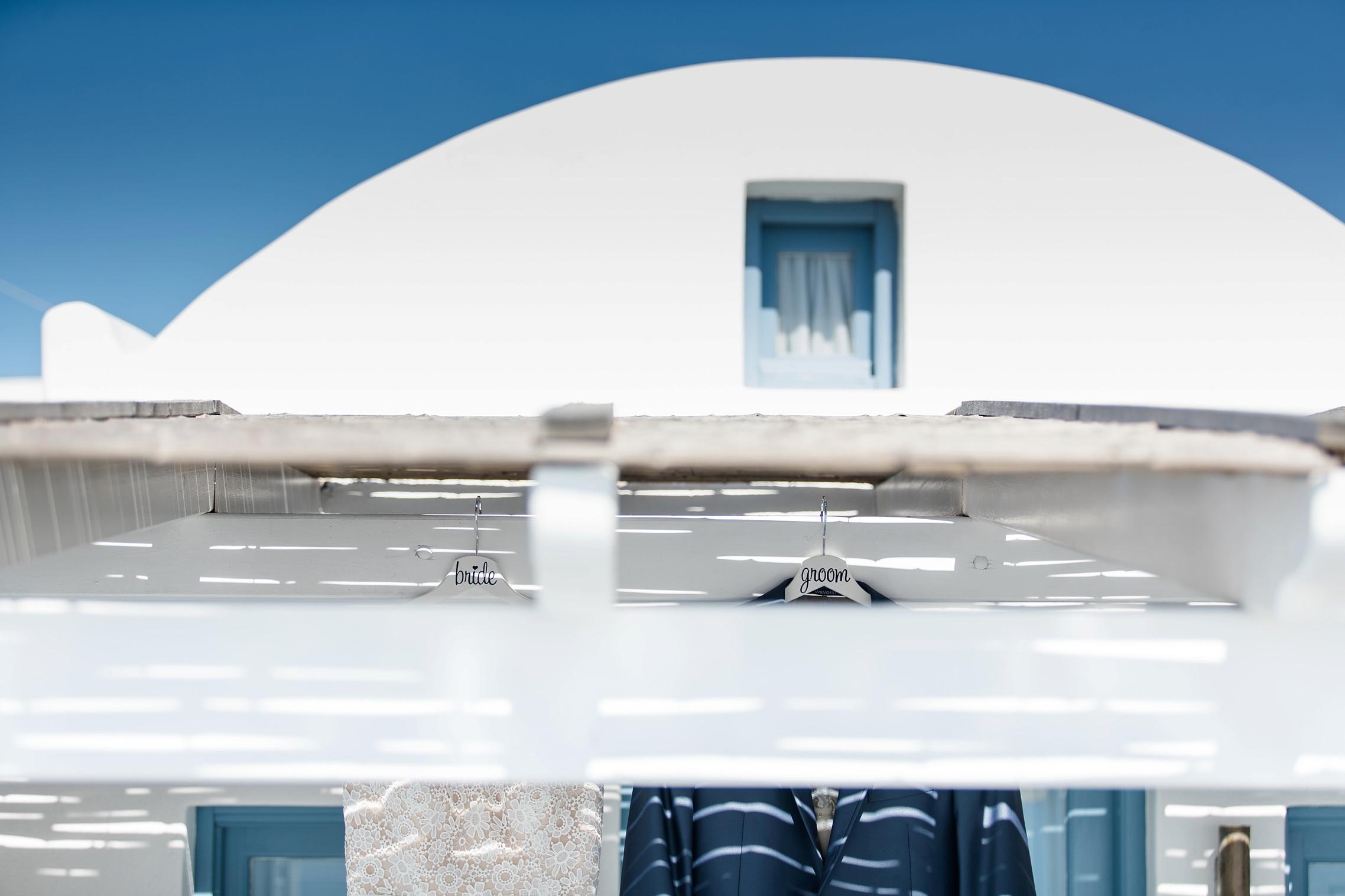 After-Wedding Santorini: Unter dem Strohdach der Appartment-Terrasse hängen das Brautkleid und der Anzug des Bräutigams an beschrifteten Kleiderhaken.