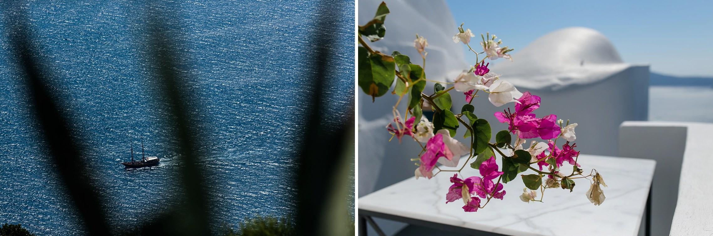 Santorini-typische Blumen und ein Blick auf das Meer mit einem Segelschiff.