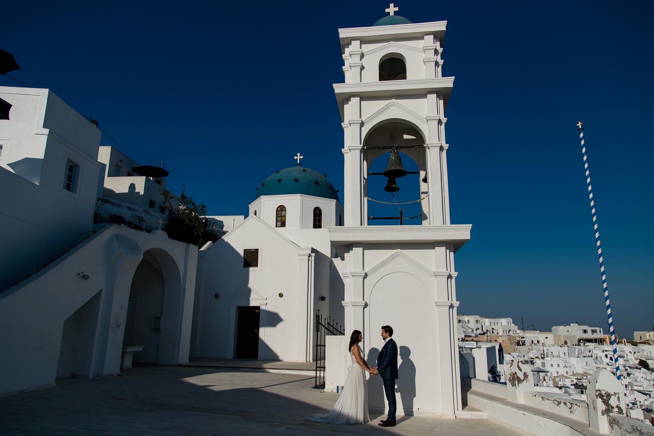 After-Wedding Santorini: Braut und Bräutigam stehen vor einer typischen Santorini-Kulisse in blau und weiß. Kirchturm und Kirchkuppel im Hintergrund.