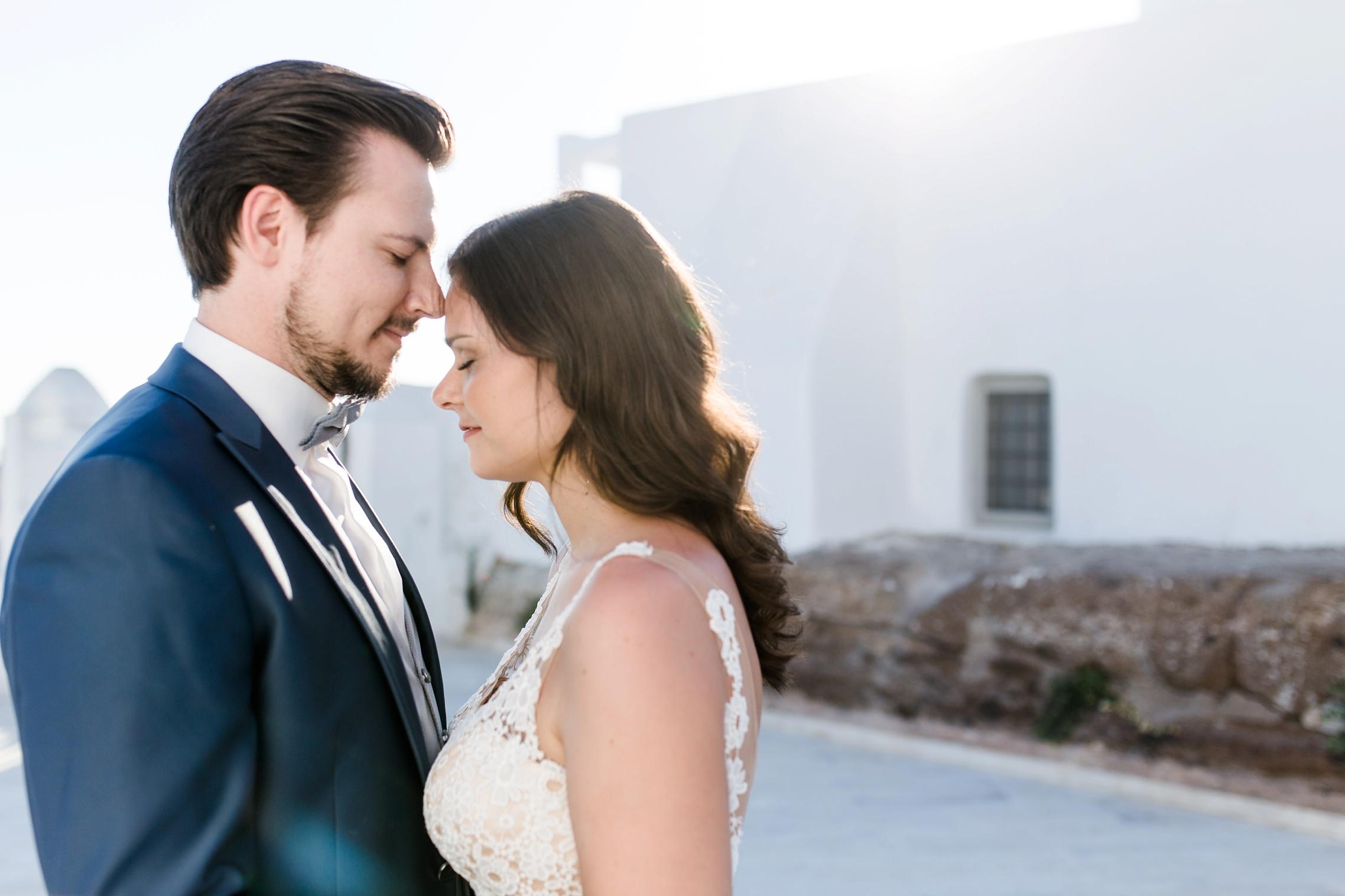 Verliebtes Hochzeitspaar im Gegenlicht auf Santorini.