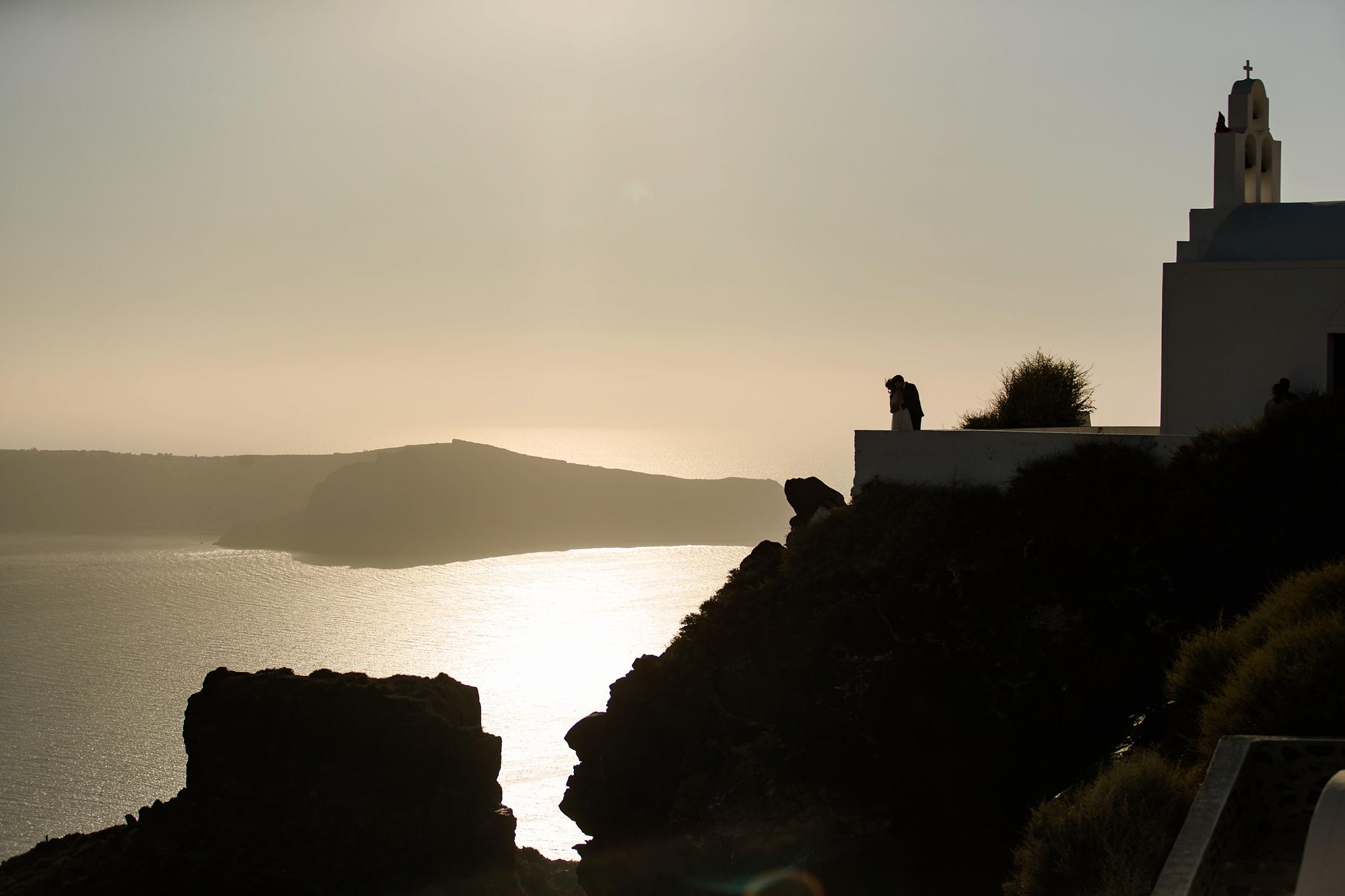 Silhouetten-Panorama-Bild mit Meerblick auf Santorini mit einem Hochzeitspaar.