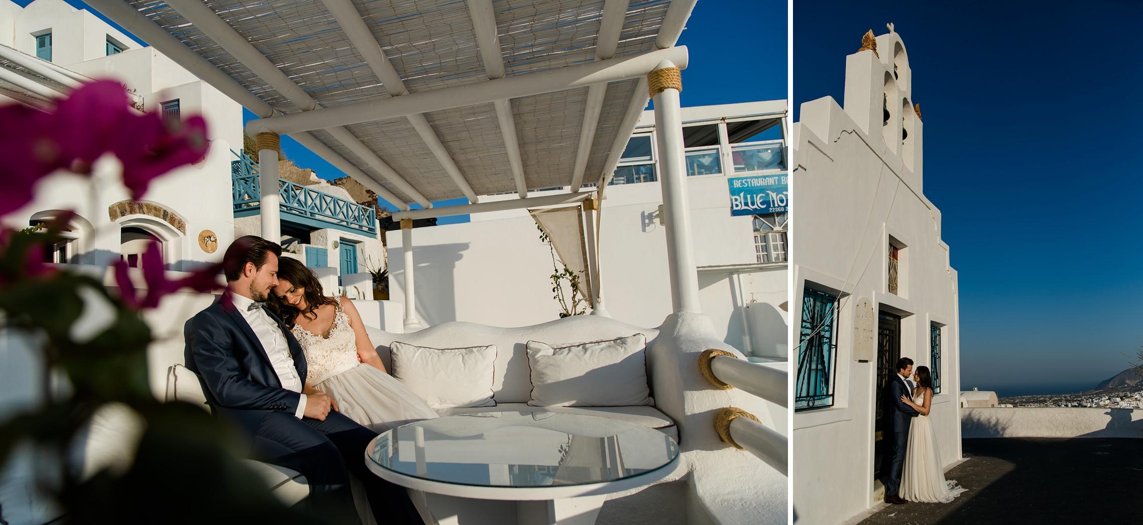 Hochzeitspaar sitzt auf einem weißen Sofa beim Sonnenuntergang auf Santorini.