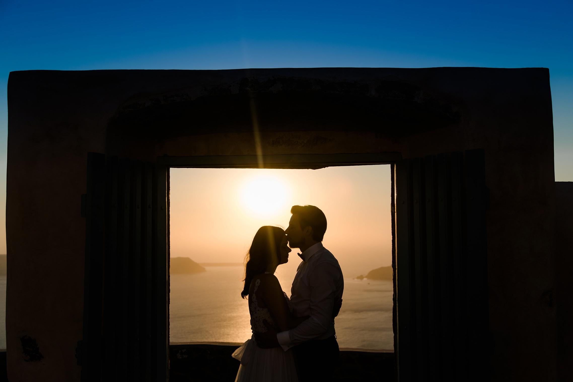 After-Wedding Santorini: Küssendes Hochzeitspaar beim Sonnenuntergang vor einem blau-orangenen Himmel.