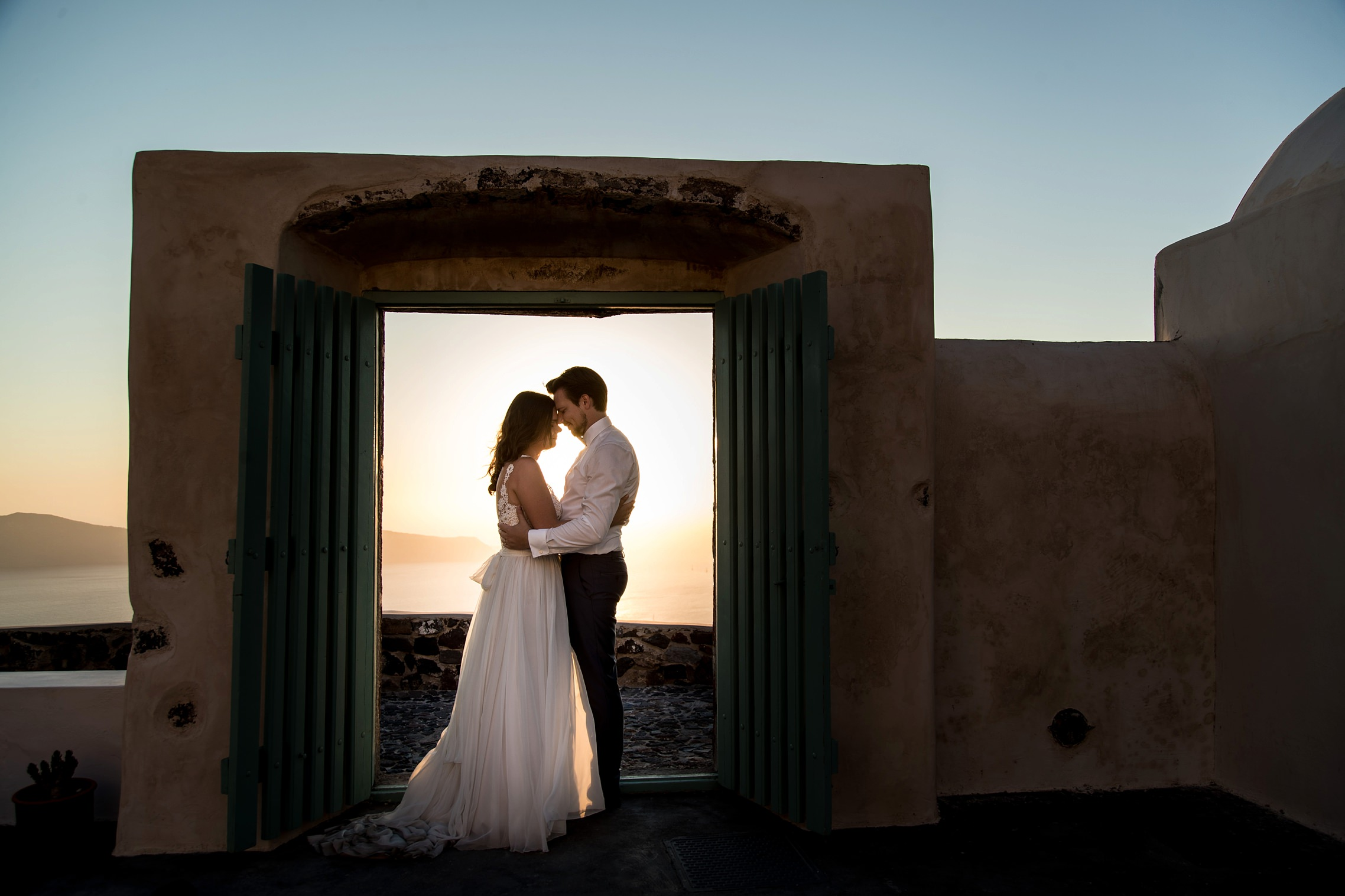 Brautpaar steht in einem Türrahmen in Imerovigli auf Santorini - Elopement in Griechenland.