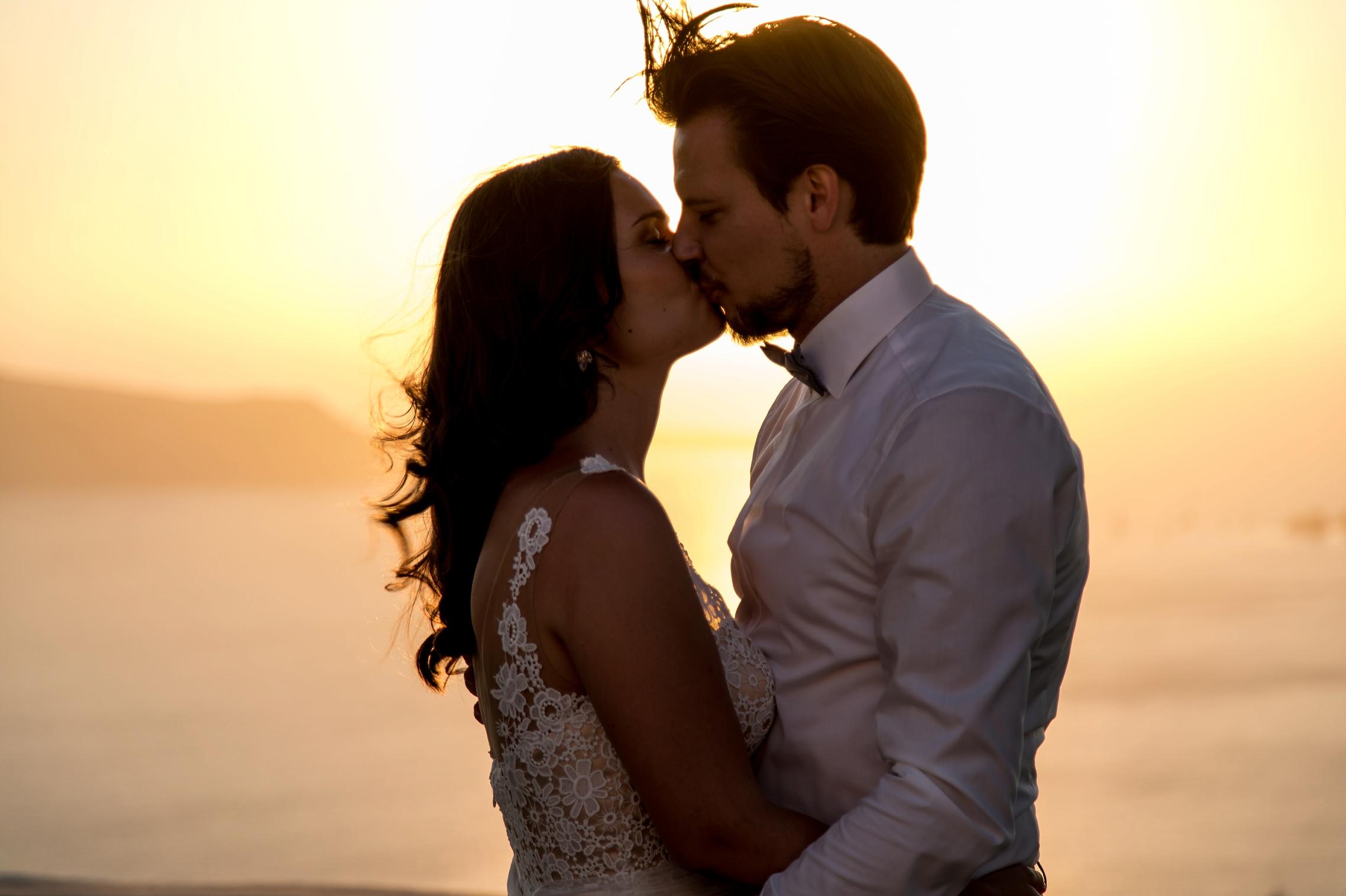 Küssendes Hochzeitspaar im Sonnenuntergang auf Santorini - Elopement in Griechenland.