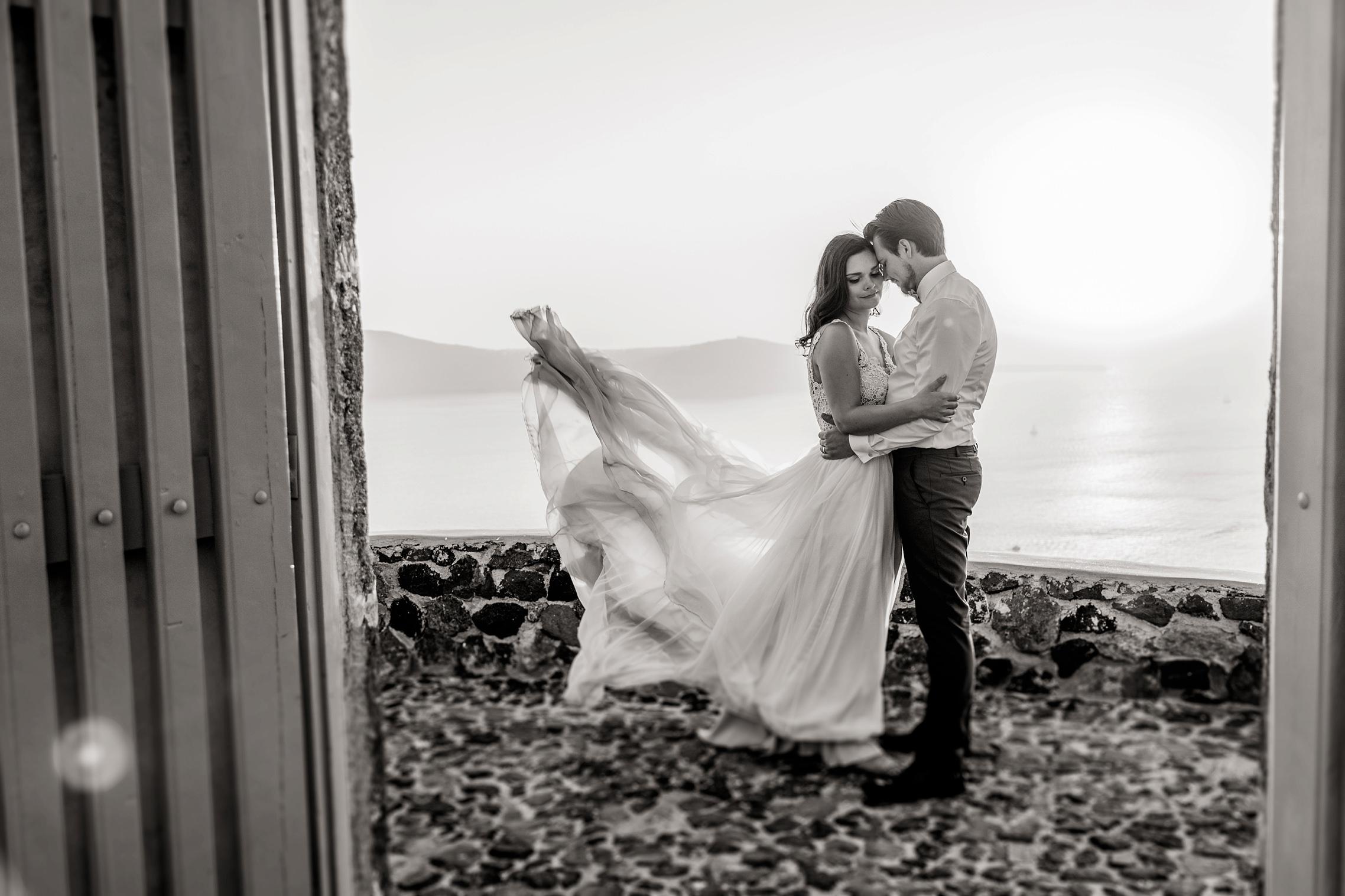 Foto in schwarzweiß: das Brautkleid fliegt in der Meeresbrise beim After-Wedding-Shooting auf Santorini.