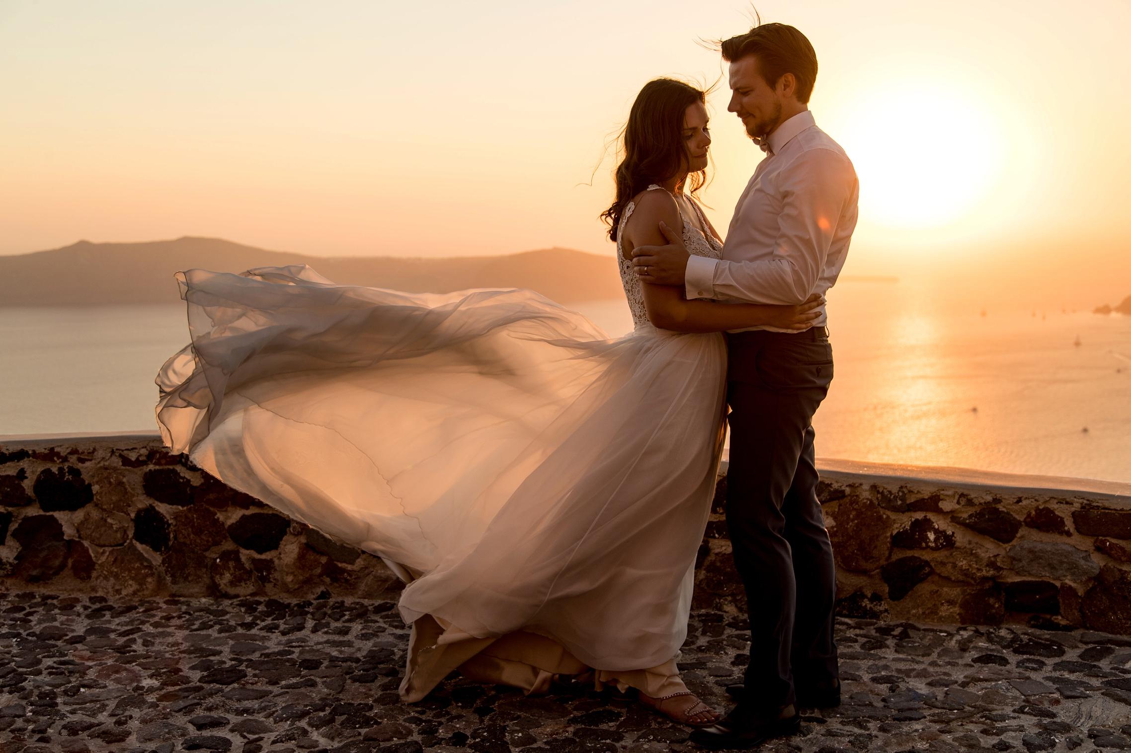 Fliegendes Brautkleid während des Sonnenunterganges beim After-Wedding-Shooting Santorini.