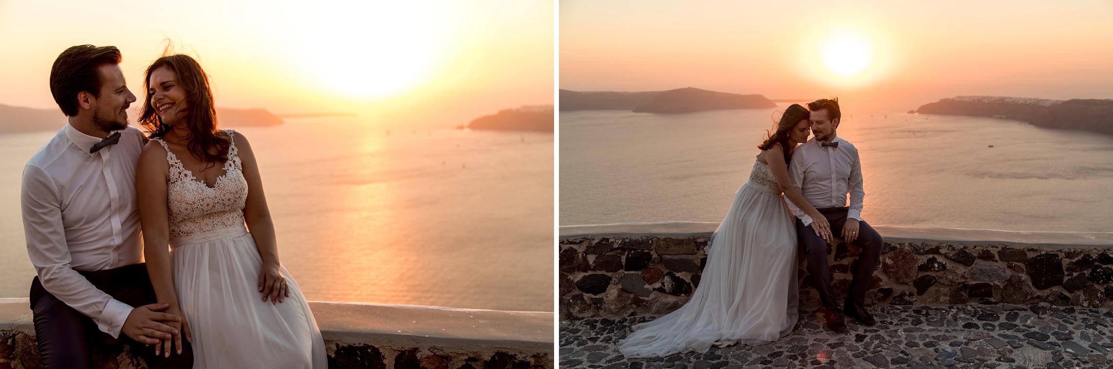 Brautpaar sitzt auf einer Steinmauer in Imerovigli, Santorini und genießt den Sonnenuntergang mit einem tollen Blick aufs Meer.