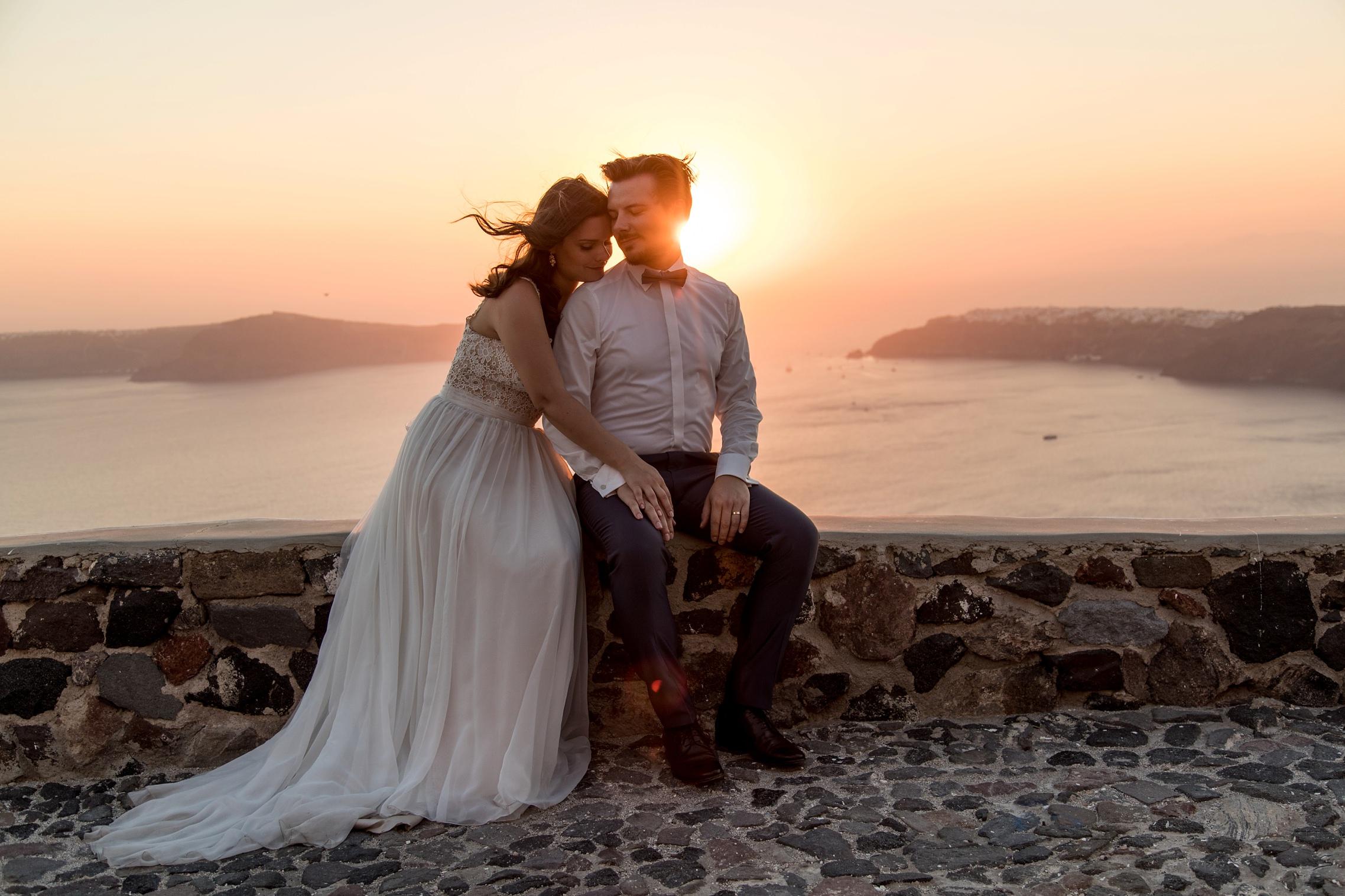 Romanisches Hochzeitspaar genießt den Sonnenuntergang auf Santorini beim After-Wedding Shooting und sitzt auf einer Steinmauer.