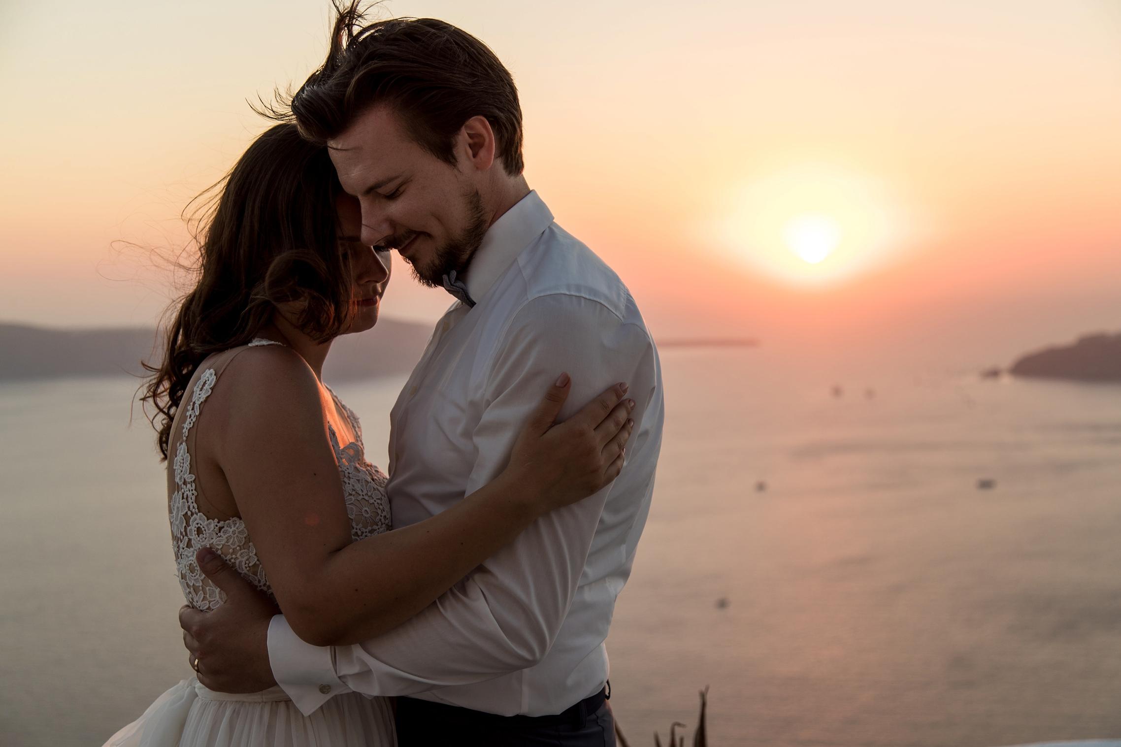 Kuschelndes Hochzeitspaar im Sonnenuntergang auf Santorini.