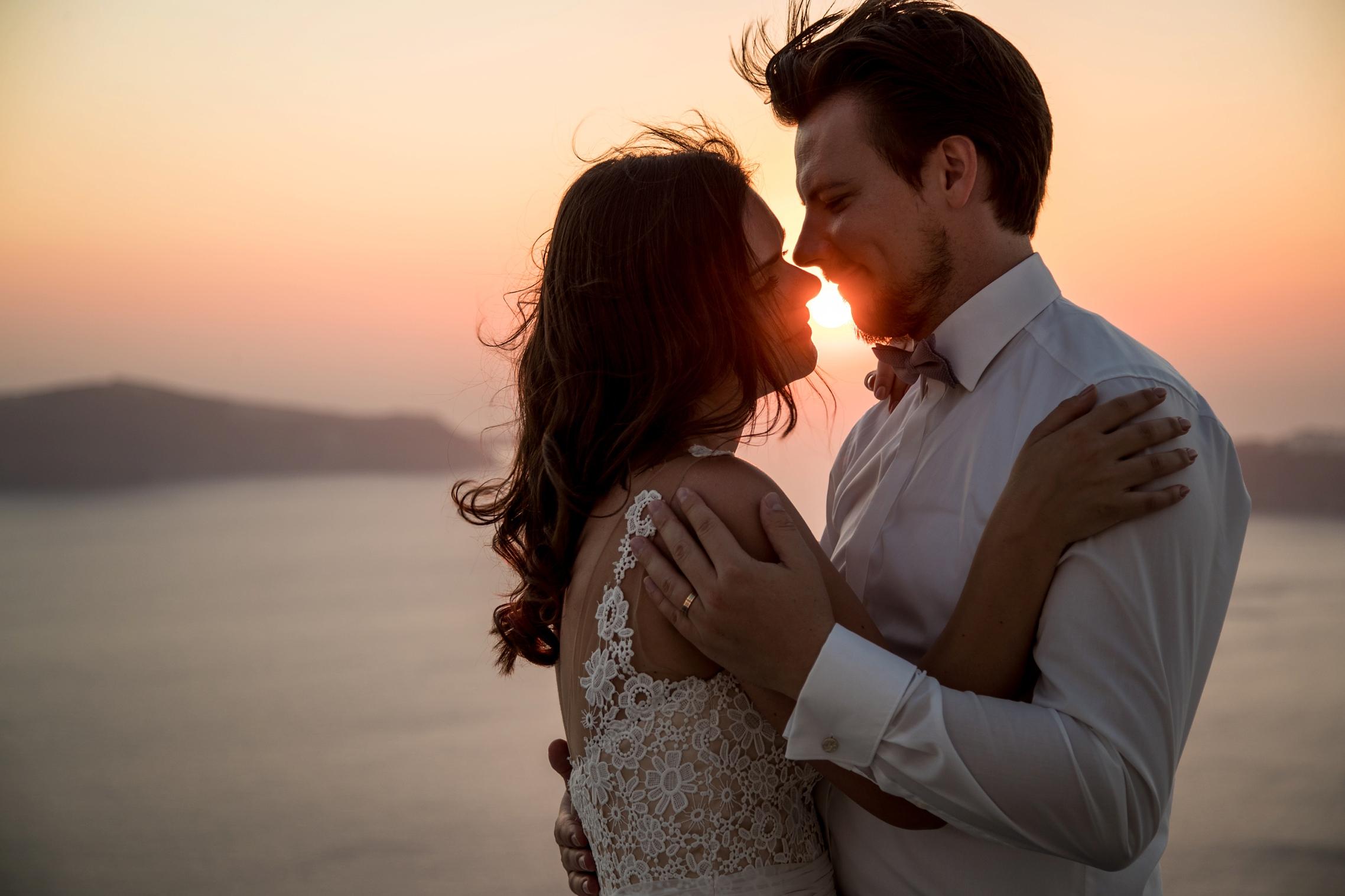 Kuschelndes Hochzeitspaar im Sonnenuntergang auf Santorini mit fliegenden Haaren.