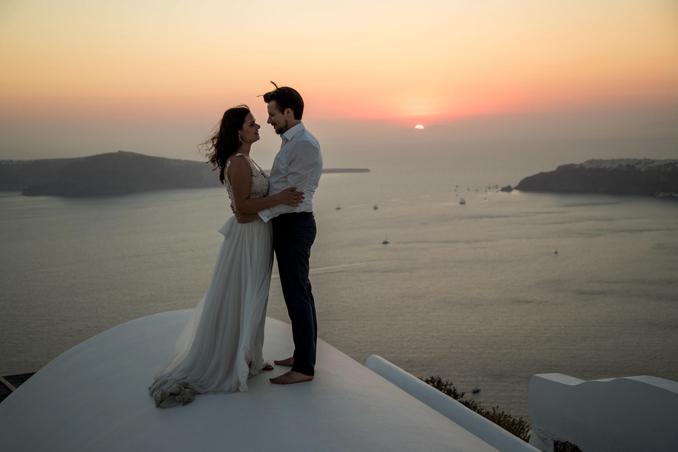 Hochzeitspaar steht über den Dächern von Santorini beim Sonnenuntergang.
