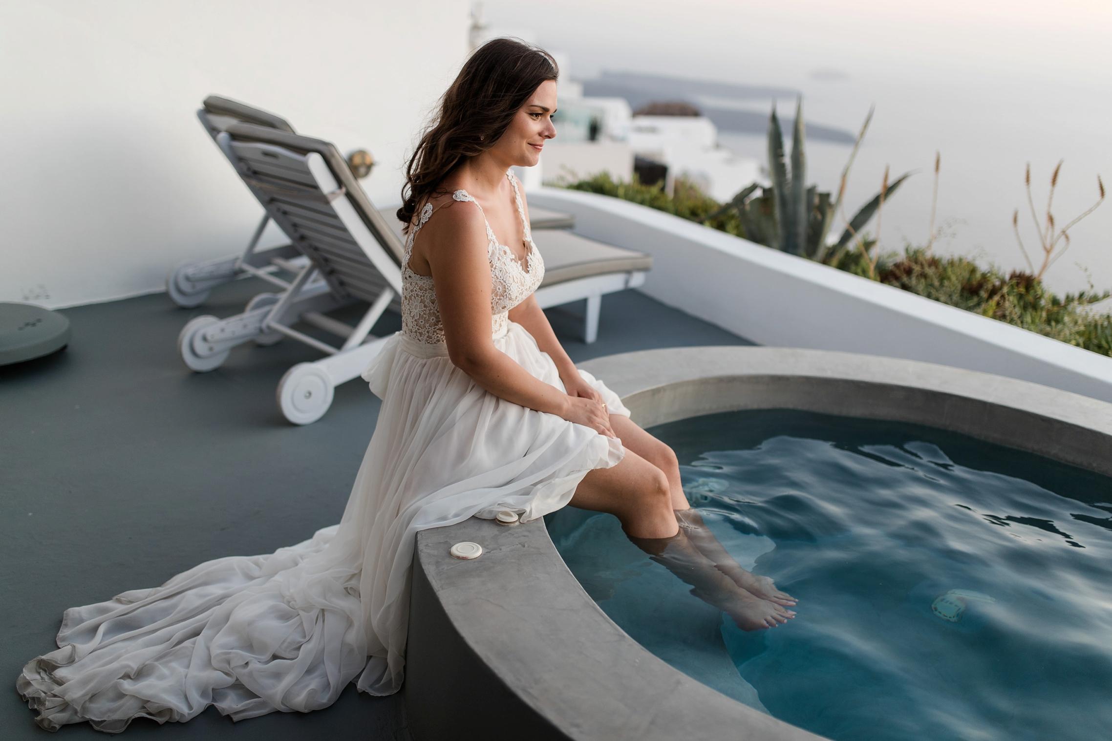 Die Braut entspannt sich am Whirlpool und hält ihre Füße ins Wasser.