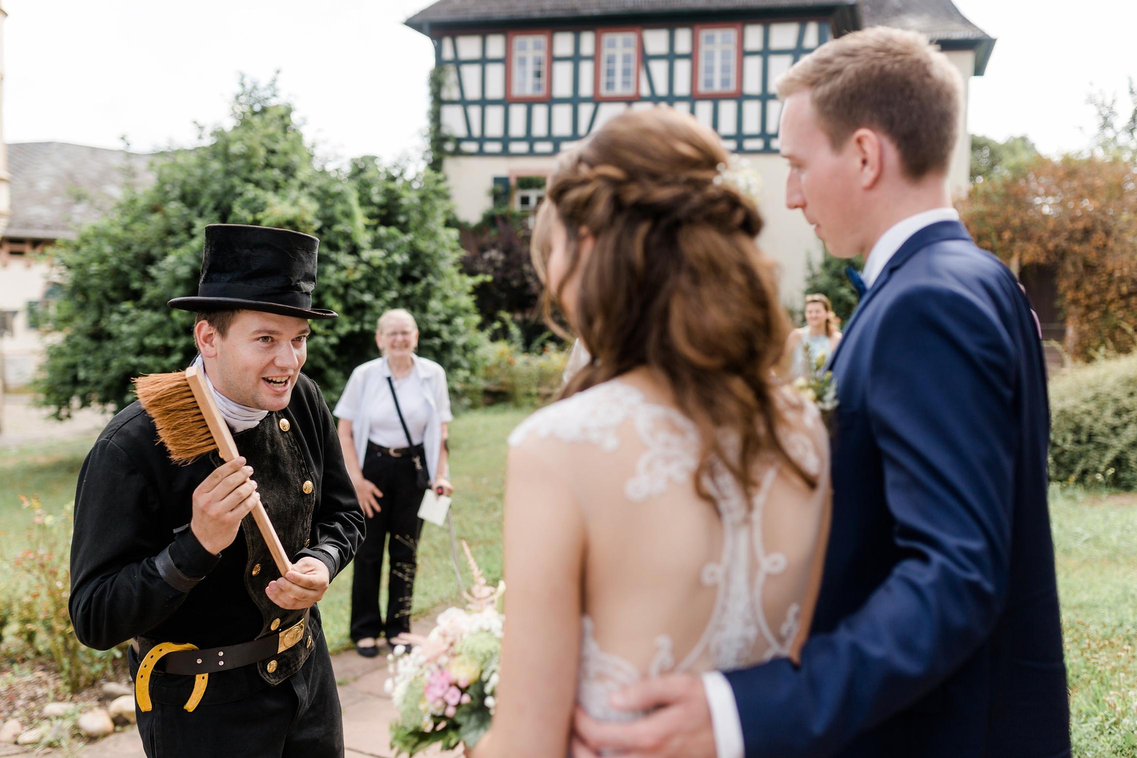 Ein Schornsteinfeger wünscht dem Hochzeitspaar viel Glück und übergibt verschiedene Gegenstände.