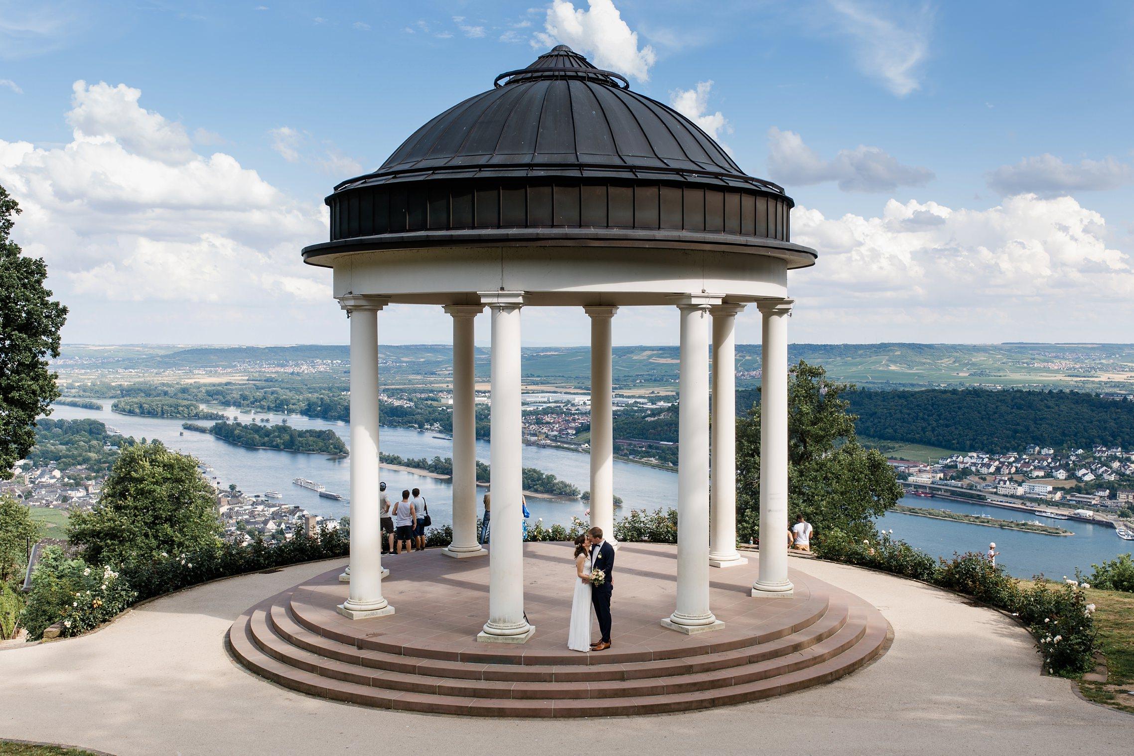 Blick über die Rheinebene mit einem Hochzeitspaar, welches im steinernen Pavillion neben der Seilbahn von Rüdesheim steht.