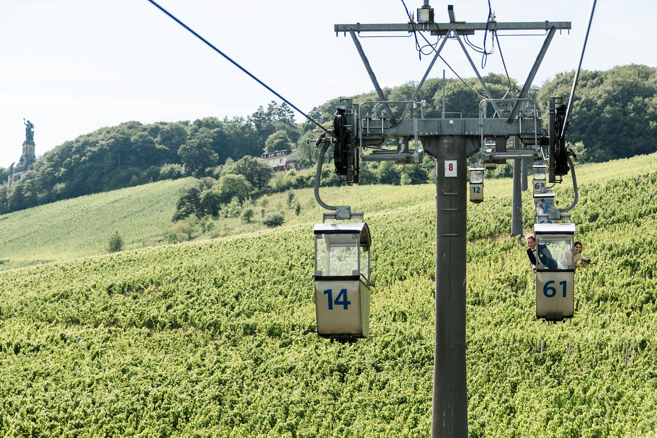 Das Hochzeitspaar schwebt in der Seilbahn über den Weinbergen von Rüdesheim. Im Hintergrund ist das Niederwald-Denkmal zu sehen.