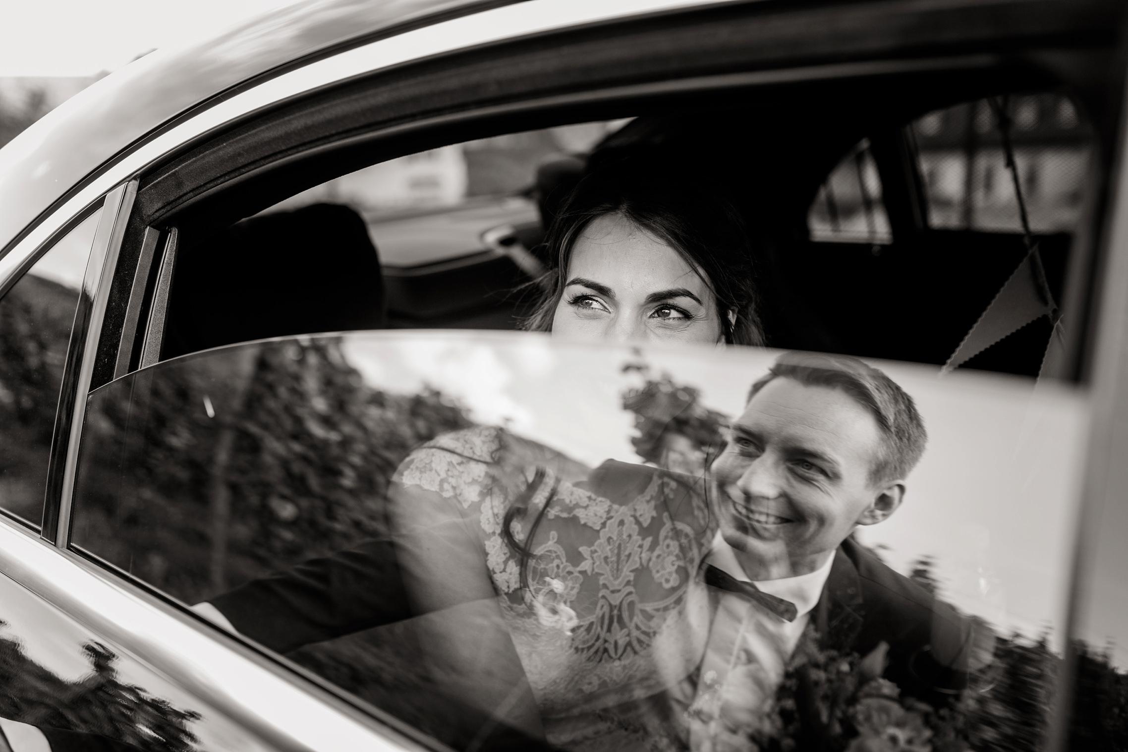 Der Bräutigam spiegelt sich in diesem schwarz-weiss Bild in der Scheibe des Hochzeitsautos und lächelt seine Frau an.