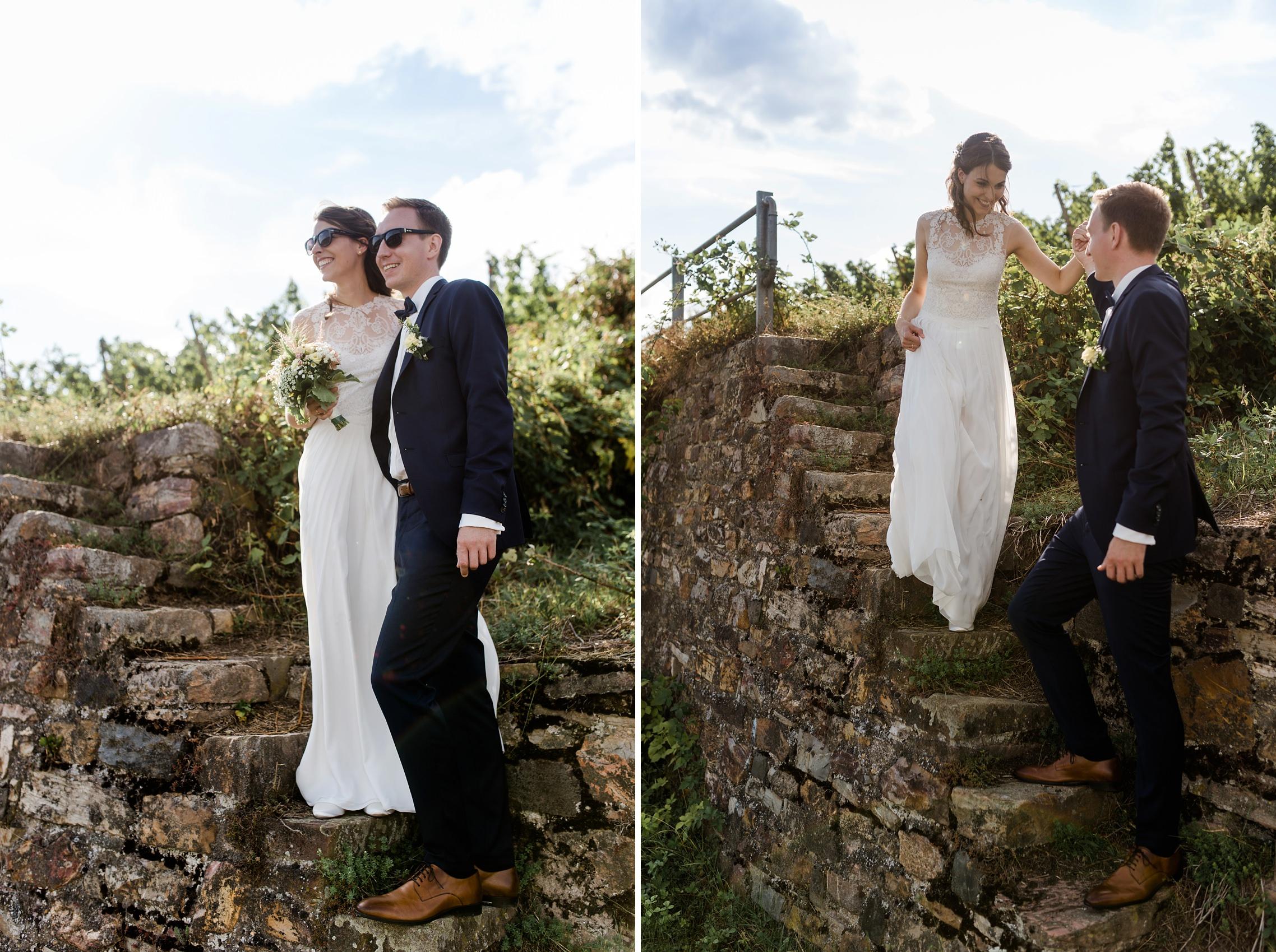 Der Bräutigam hilft seiner Braut in den Weinbergen von Rüdesheim eine Steintreppe herunter.