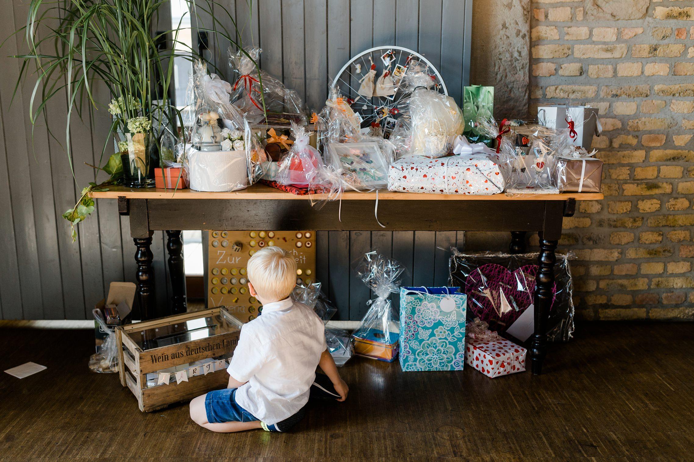 Ein Kind sitzt verträumt vor dem Geschenketisch des Hochzeitspaares.