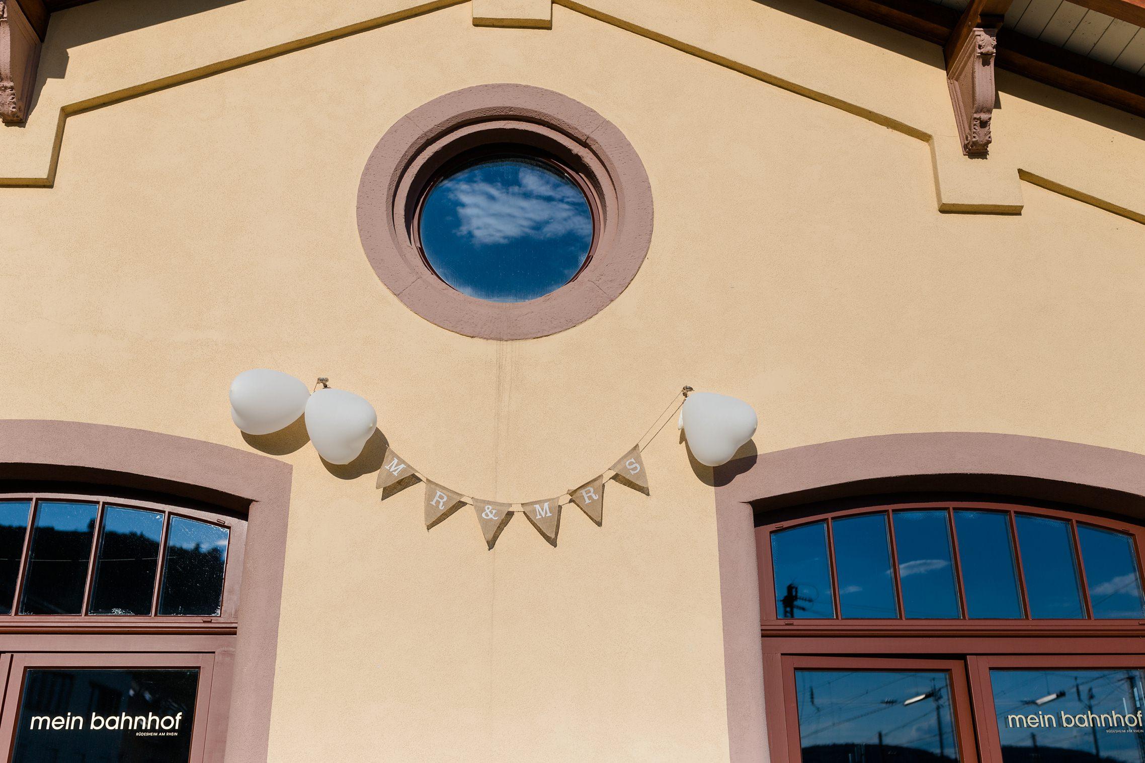 """Fassade des Bahnhof in Rüdesheim mit einer Wimpelkette auf der """"Mister und Misses"""" steht."""