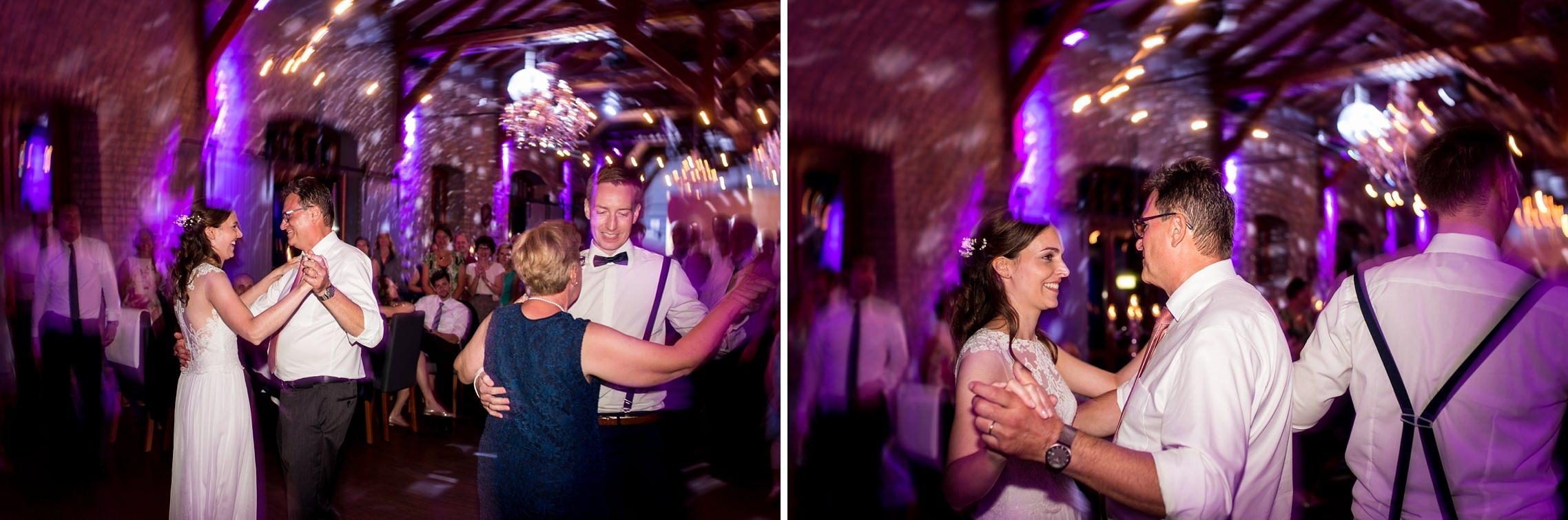 Der Bräutigam tanzt mit seiner Mutter während die Braut mit ihrem Vater das Tanzbein schwingt.