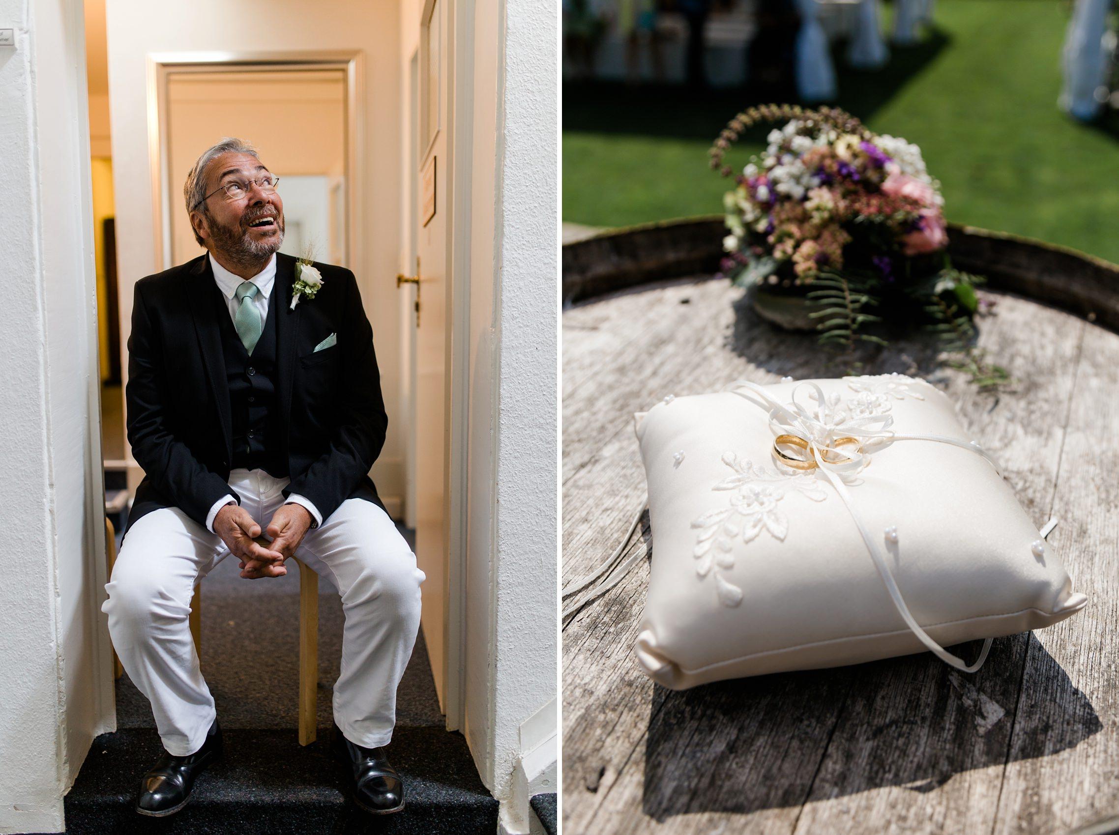 Der Brautvater sitzt auf einem Stuhl im Treppenhaus im Weingut Fitz-Ritter in Bad Dürkheim und wartet auf seine Tochter. Daneben sind die Trauringe auf dem Ringkissen zu sehen.