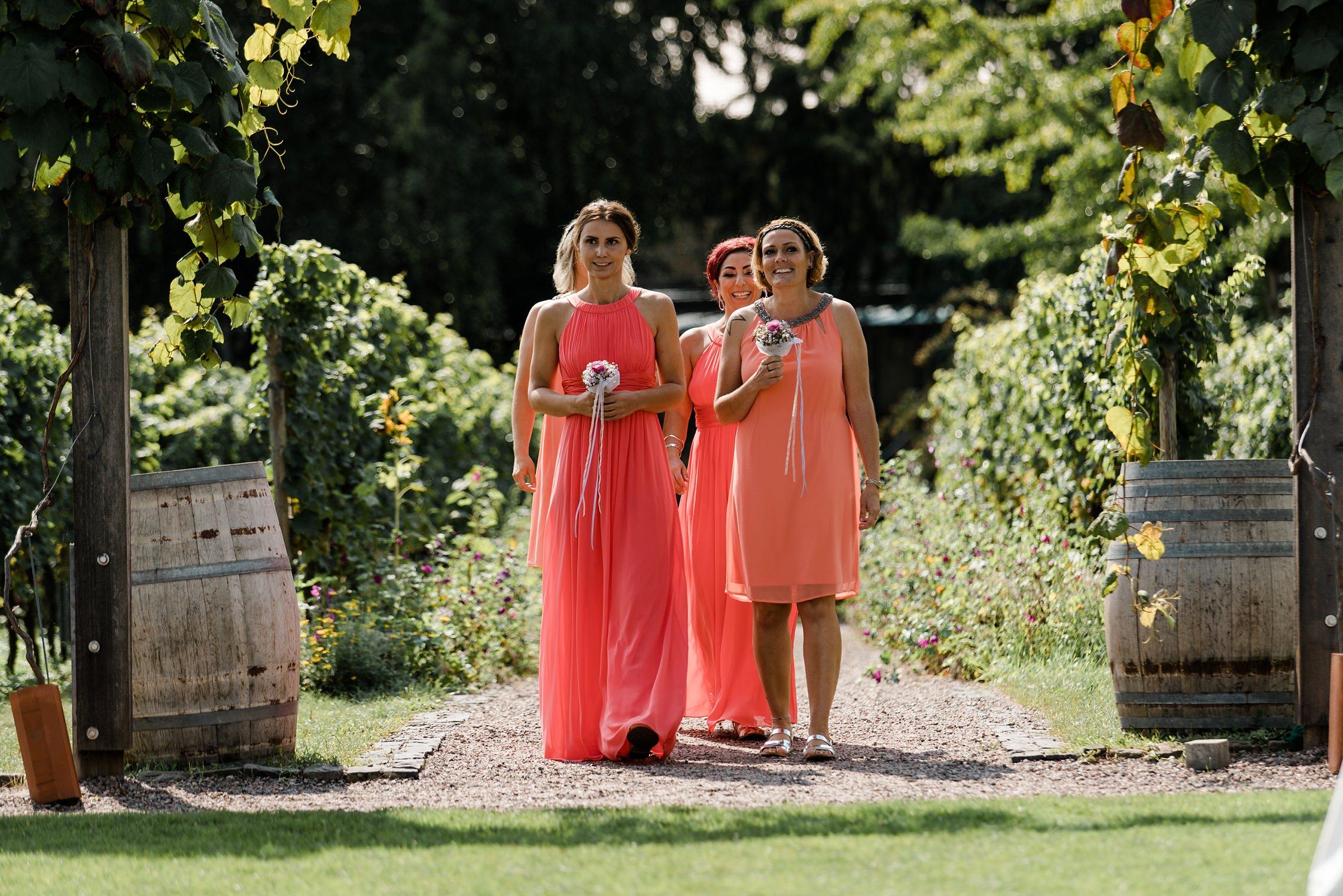 Die Brautjungfern laufen vorneweg und verdecken noch die Braut im Weingut Fitz-Ritter in Bad Dürkheim.