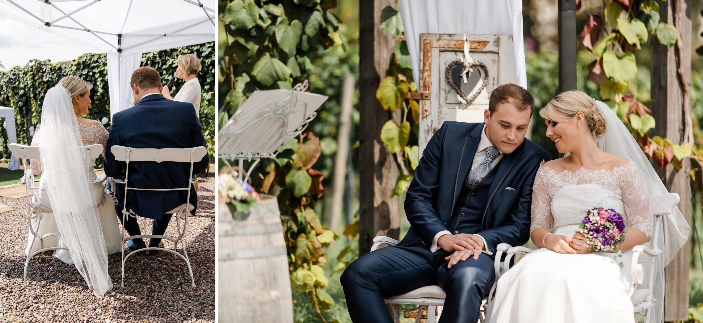 Das Brautpaar unterhält sich lächelnd während der freien Trauung in der RebArena im Weingut Fitz-Ritter in Bad Dürkheim.