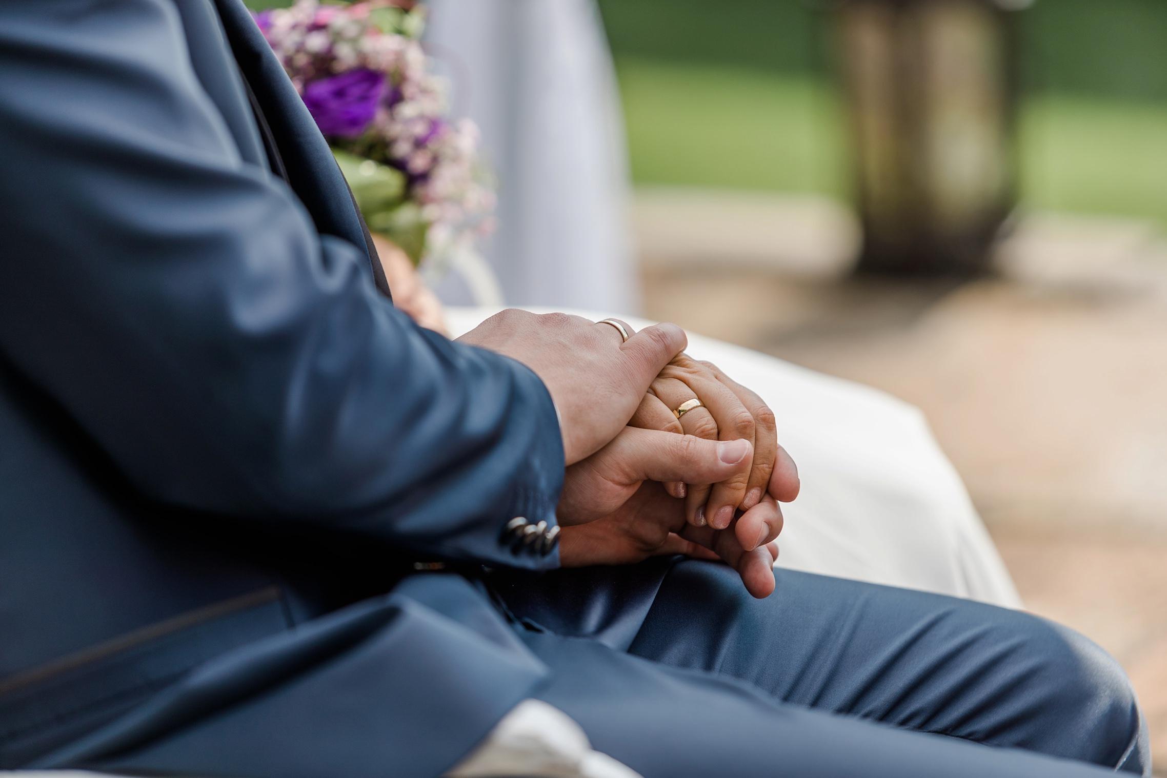 Detailaufnahme der Hände des Brautpaares mit den frisch angesteckten Ringen.