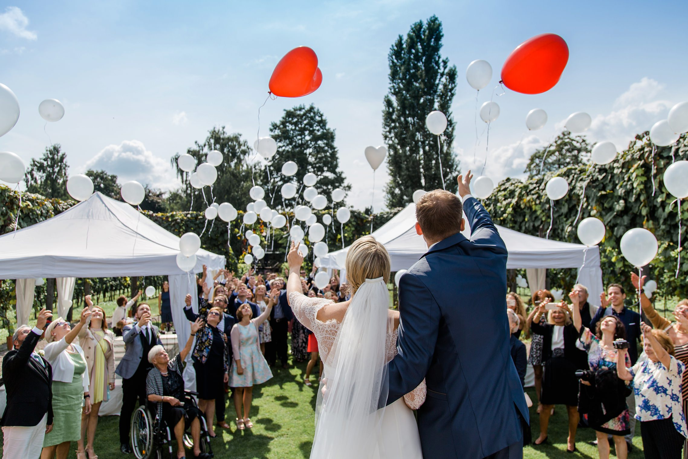 Das Hochzeitspaar lässt zusammen mit den Gästen in der RebArena im Weingut Fitz-Ritter die Luftballons steigen.