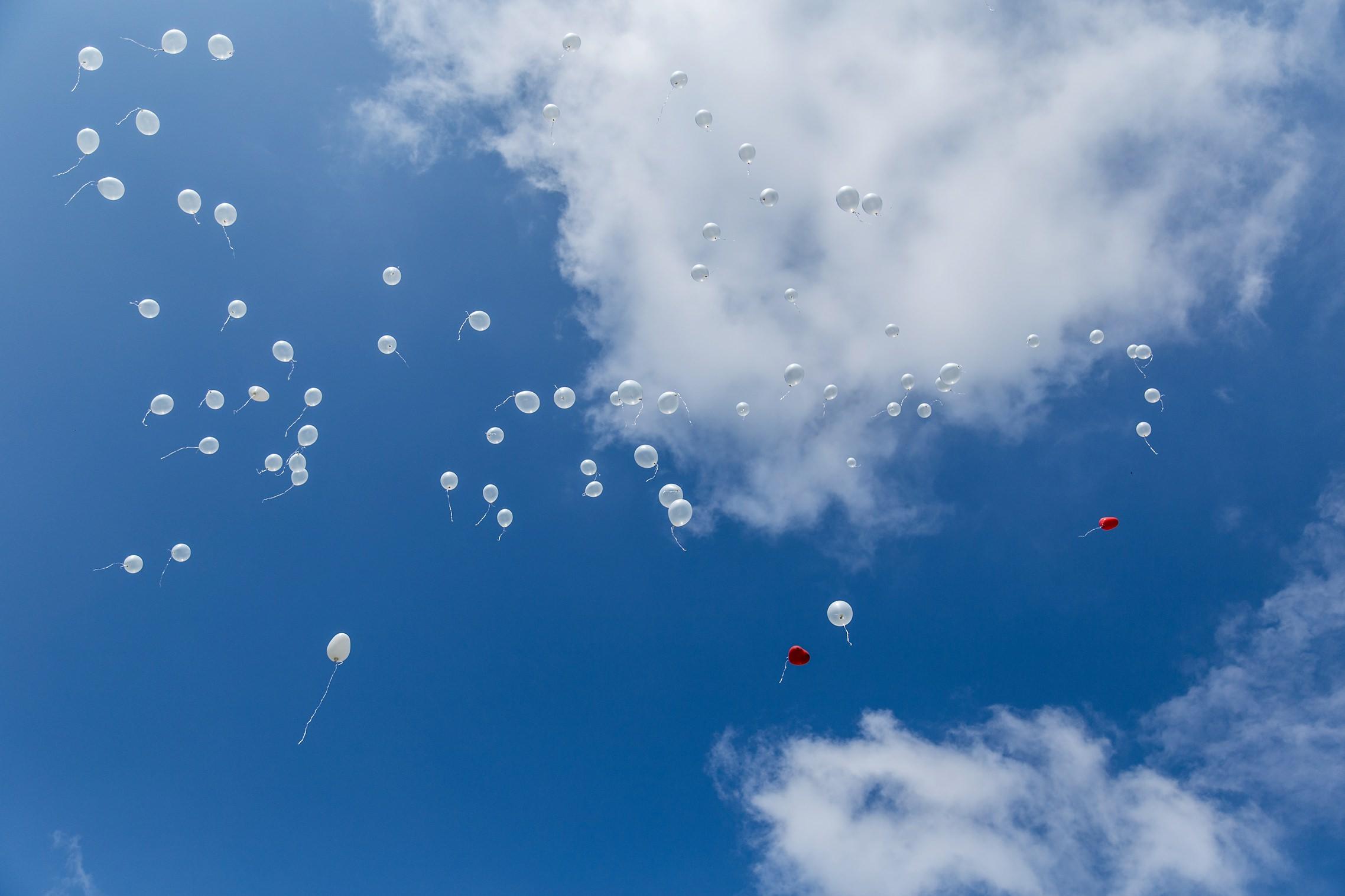 Weiße Hochzeits-Luftballons und zwei rote Ballons im blauen Himmel.