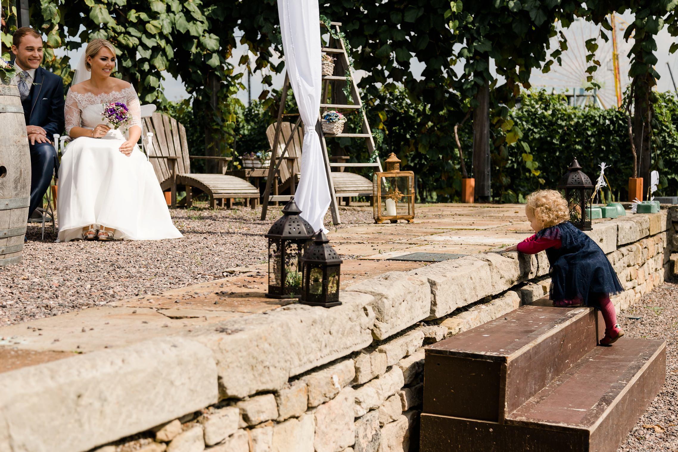 Ein kleines Kind klettert die Treppenstufen zur Bühne der RebArena hinauf und möchte direkt bei dem Hochzeitspaar sein.