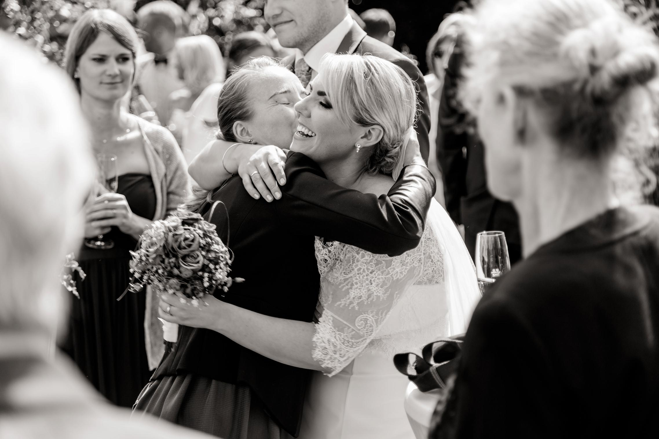 SW-Bild der Braut, die während der Gratulationen herzlich von einem Gast in den Arm genommen und geküsst wird.