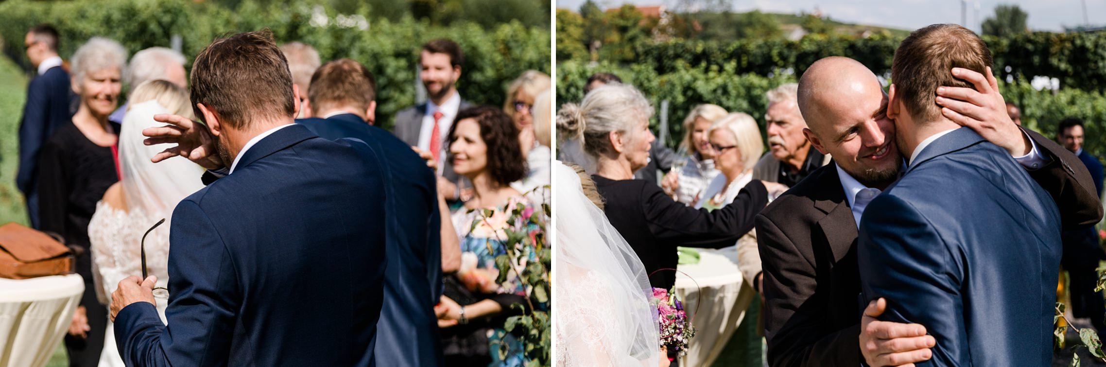 Emotionen während der Gratulationen für das Brautpaar: ein Gast wischt sich die Tränen weg, während ein anderer Gast den Bräutigam herzlich umarmt.