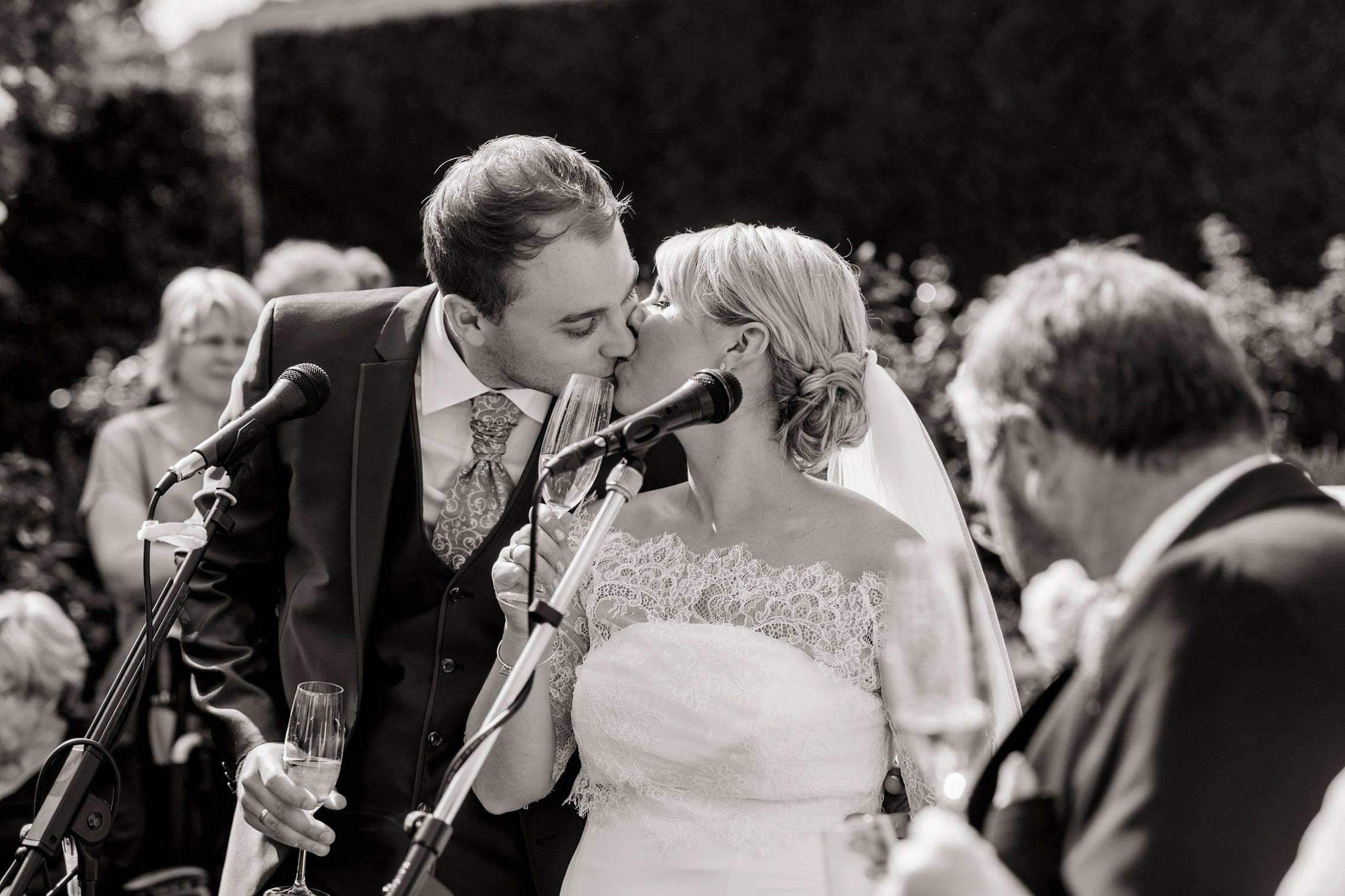 Romantisches Kuss-Bild des Hochzeitspaares in schwarz-weiß während des Sektempfangs.