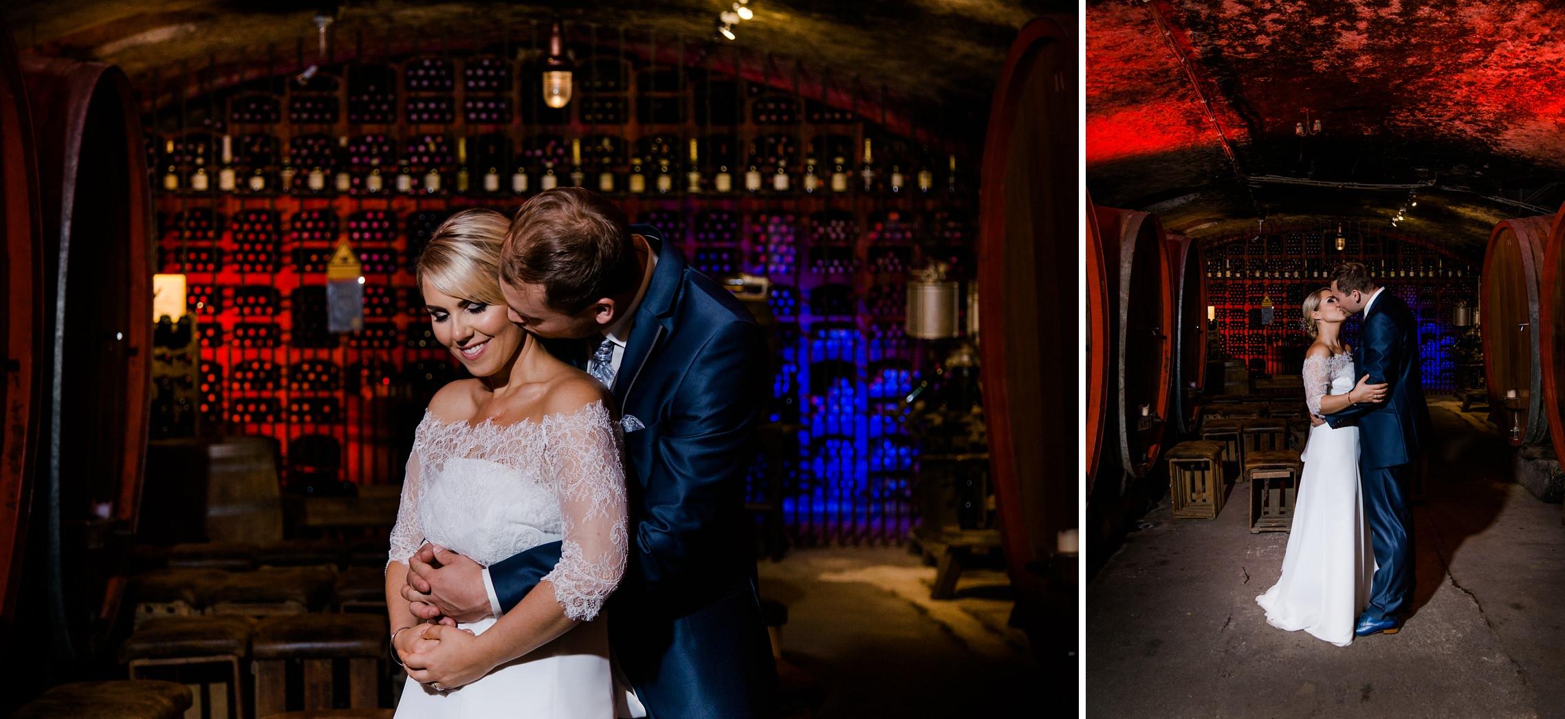 Brautpaar-Shooting im Gewölbe-Weinkeller des Fitz-Ritter in Bad Dürkheim. Im Hintergrund ist ein Flaschenlager mit kräftiger roter und blauer Farbe zu sehen.