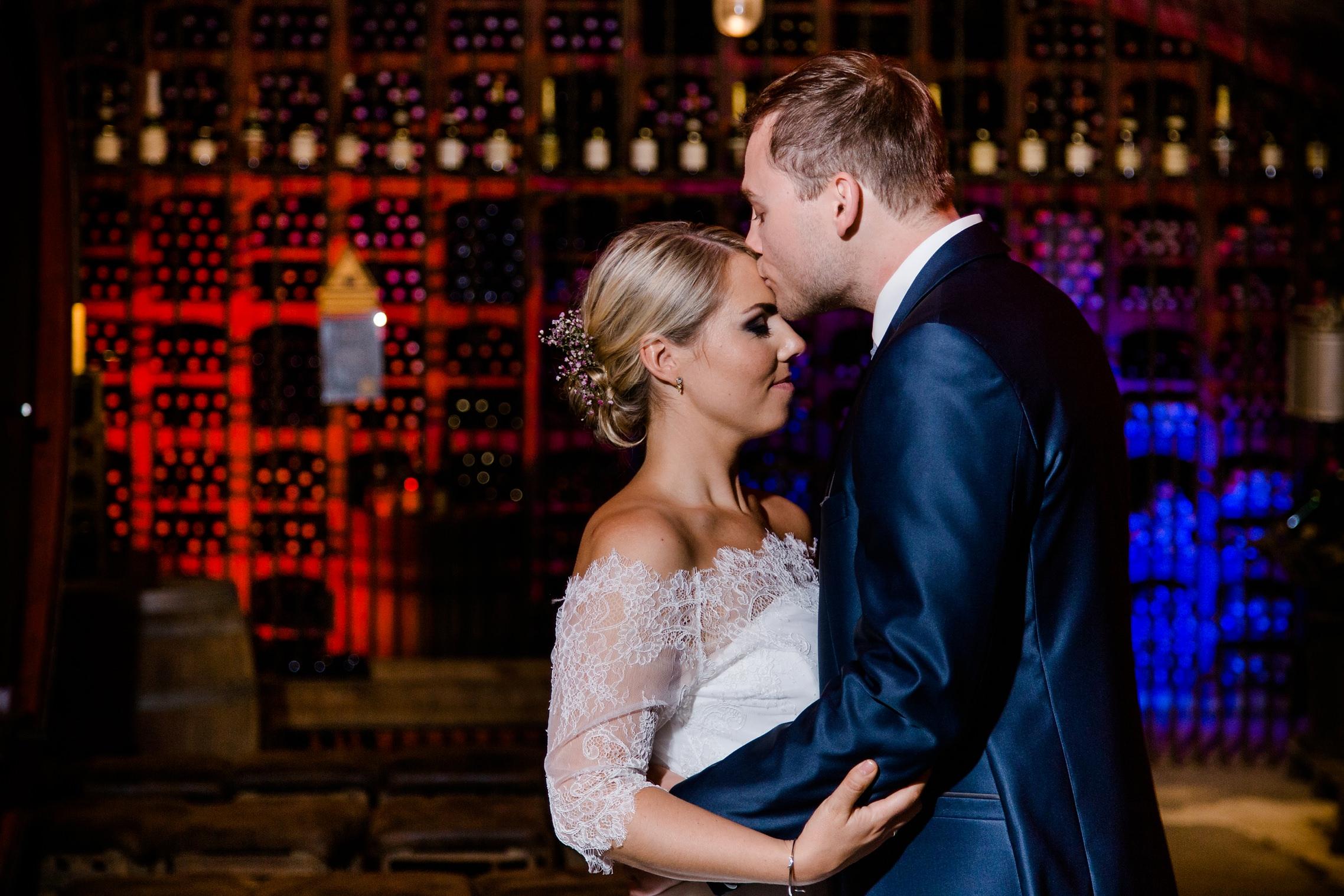 Romantisches Brautpaar-Shooting im Keller des Weingutes Fitz-Ritter in Bad Dürkheim. Der Bräutigam küsst seine Frau zärtlich auf die Stirn.